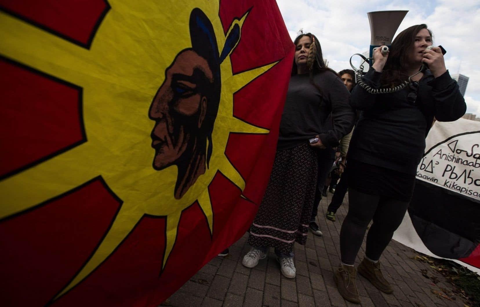 Des manifestants brandissant un drapeau mohawk lors des audiences torontoises de l'Office national de l'énergie sur l'inversion du flux du pipeline 9 (photo d'archives).