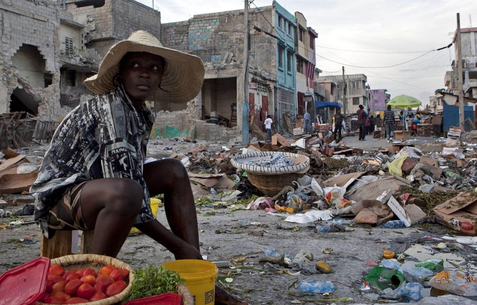 Depuis le tristement célèbre séisme qui l'a dévastée, Haïti tente de se relever. Ici, une femme vend des fruits au milieu des ruines de Port-au-Prince, un an après les événements.