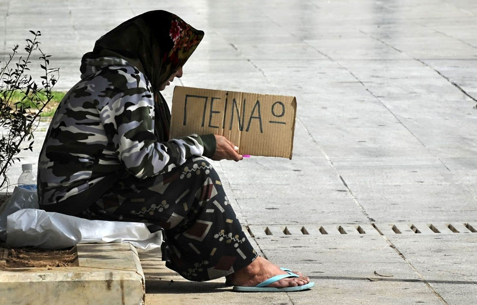 À Athènes, une femme tient une petite affiche disant simplement«j'ai faim».