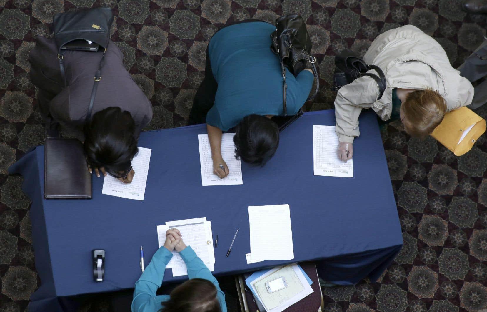 Des chercheuses d'emploi s'inscrivent à une «foire de l'emploi», à Dallas, une occasion de rencontrer d'éventuels employeurs. Plusieurs chômeurs qui avaient abandonné leur recherche d'emploi ont repris espoir au cours du mois de mars, ce qui a une incidence sur le taux de chômage.