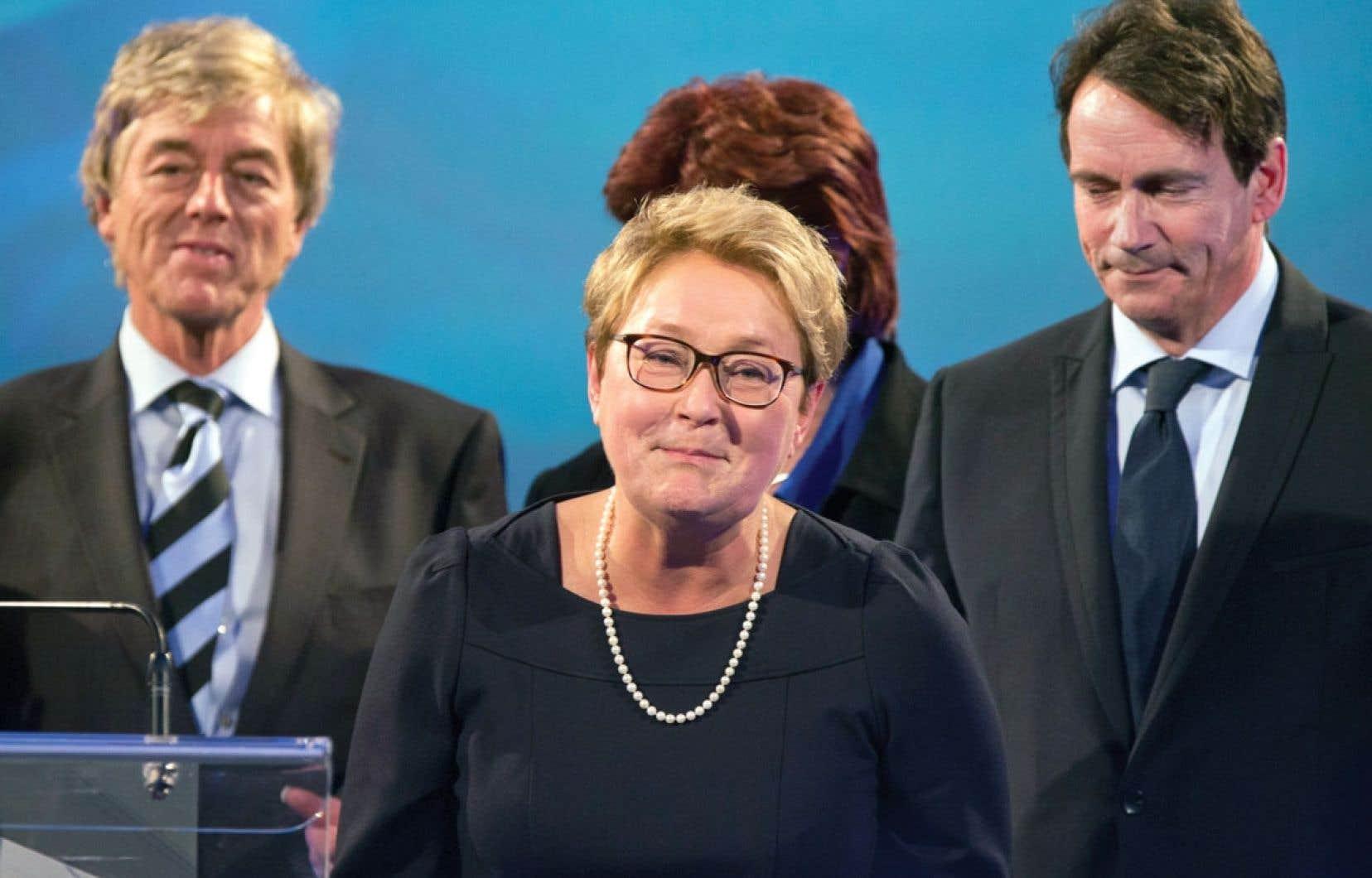 Pauline Marois annonçant son départ aux militants du Parti québécois lundi soir en présence de son mari, Claude Blanchet, et de Pierre Karl Péladeau.