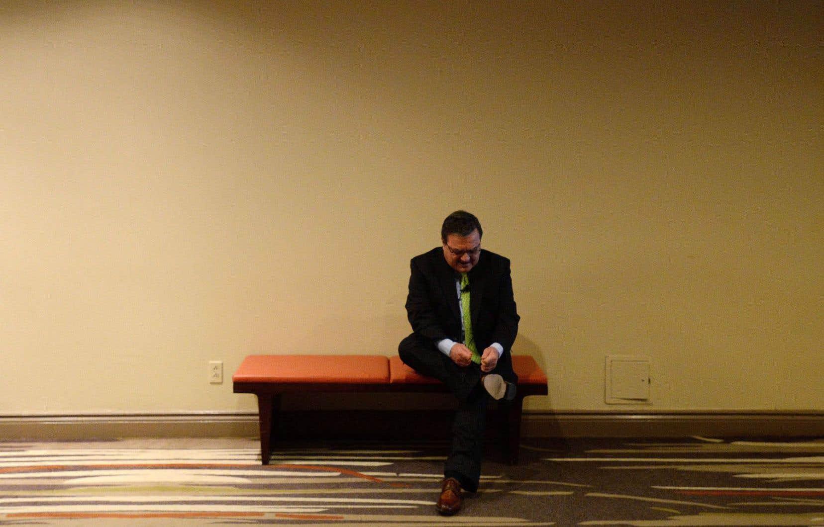 Jim Flaherty, que l'on voit ici lacer ses souliers avant d'expliquer à un auditoire son budget de février2014, est décédé subitement jeudi.