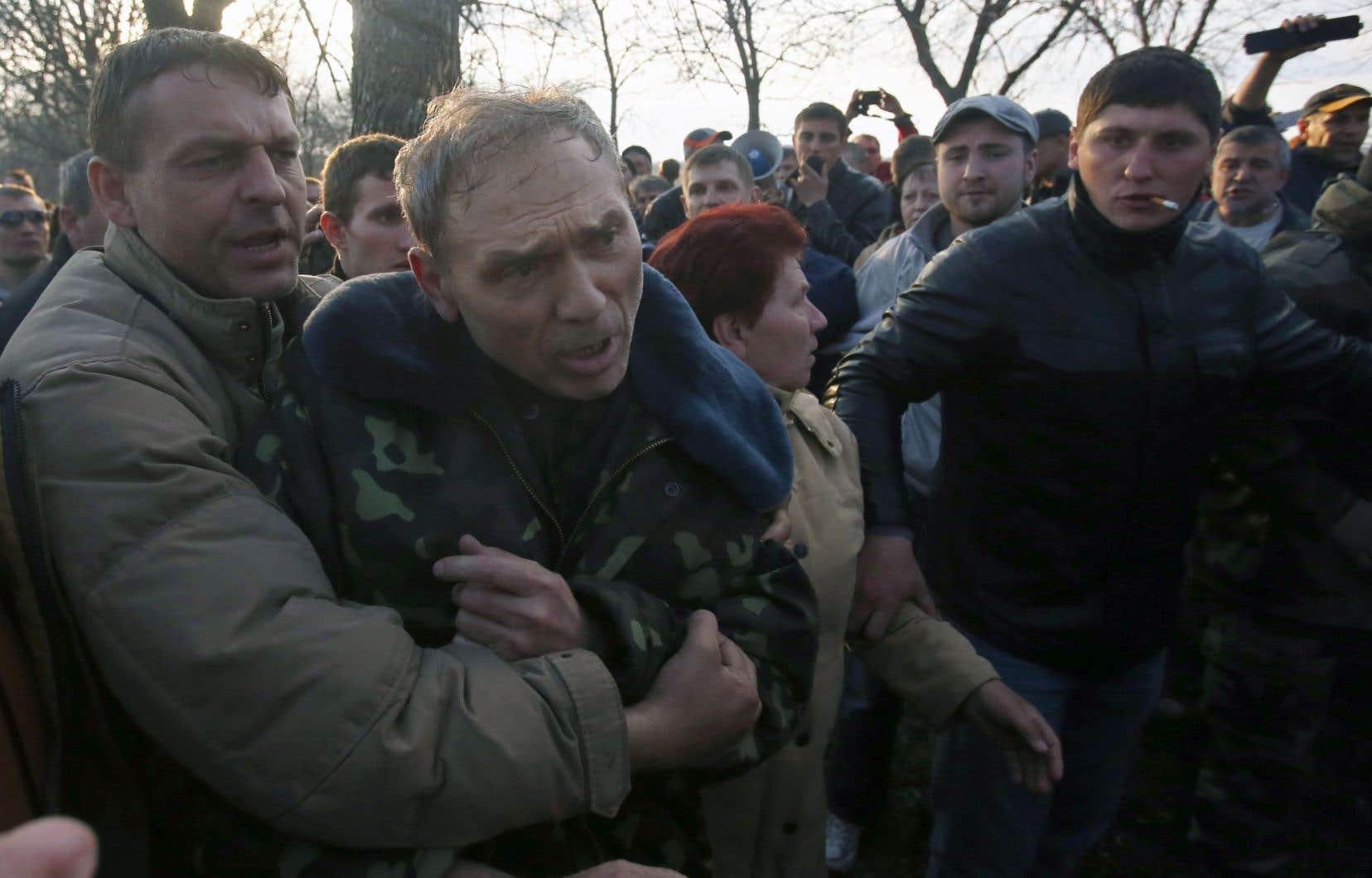 Des activistes pro-Russes s'en sont pris lundi au général Vassyl Kroutov, numéro deux des services de sécurité ukrainiens (SBU) et commandant de «l'opération antiterroriste» (au centre), après que ce dernier eut pris la parole à l'extérieur de l'aéroport de Kramatorsk, près de Slaviansk, dans l'est de l'Ukraine, où des échauffourées auraient fait des blessés.