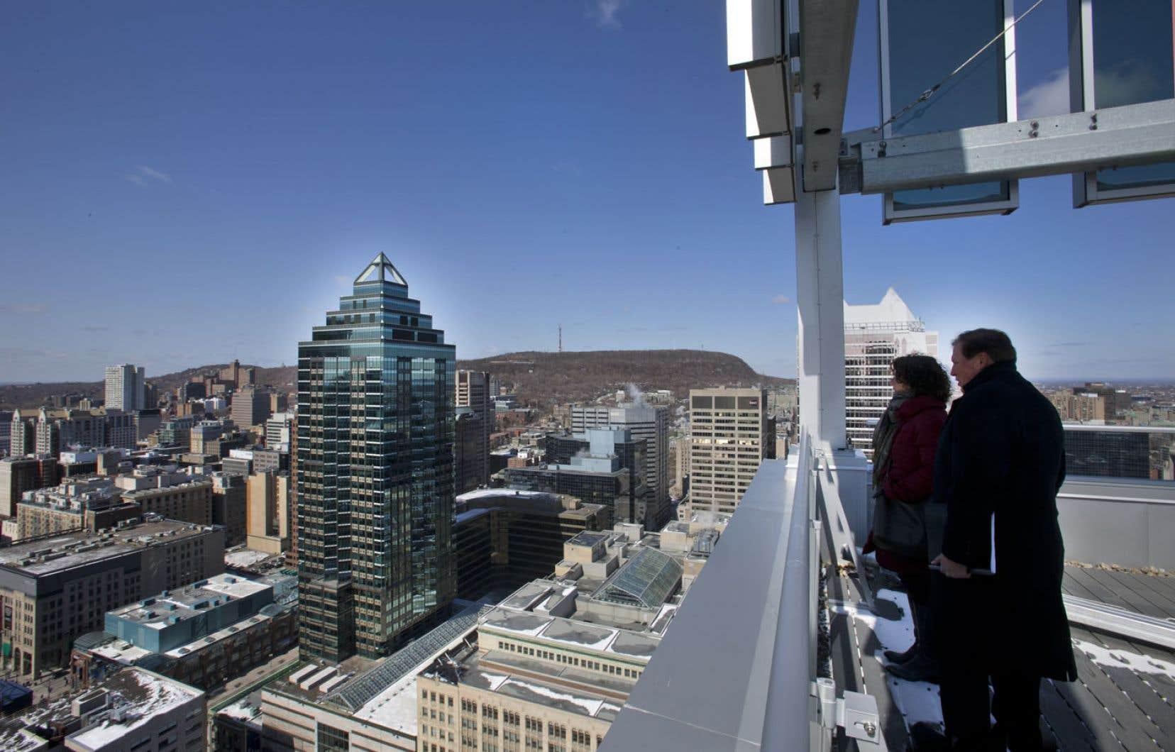 Du sommet de L'Altitude, gratte-ciel de 33 étages à l'angle des rues University et Cathcart, des visiteurs contemplent les vues du centre-ville de Montréal.