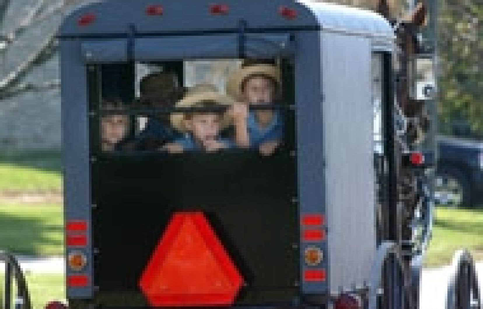 Des enfants de la communauté amish de Nickel Mines se promènent en calèche et regardent tous ces journalistes et ces policiers qui ont envahi leur ville depuis le tragique attentat survenu dans leur école.