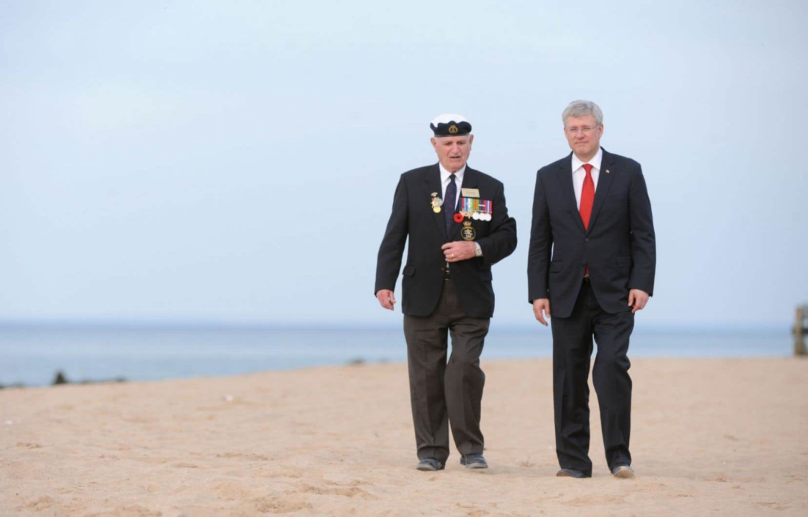 Le premier ministre Stephen Harper s'entretient avec un ancien combattant de la Deuxième Guerre mondiale lors d'une visite à Juno Beach, vendredi.