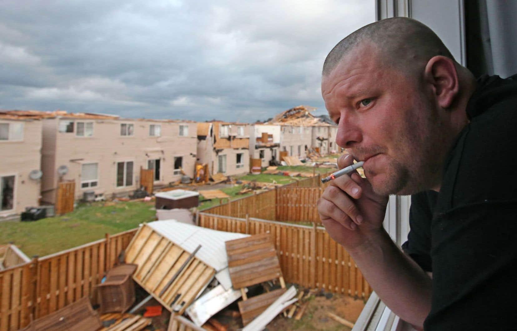 Un résident de Angus observe les dégâts causés aux résidences de ses voisins par une violente tempête, mardi.