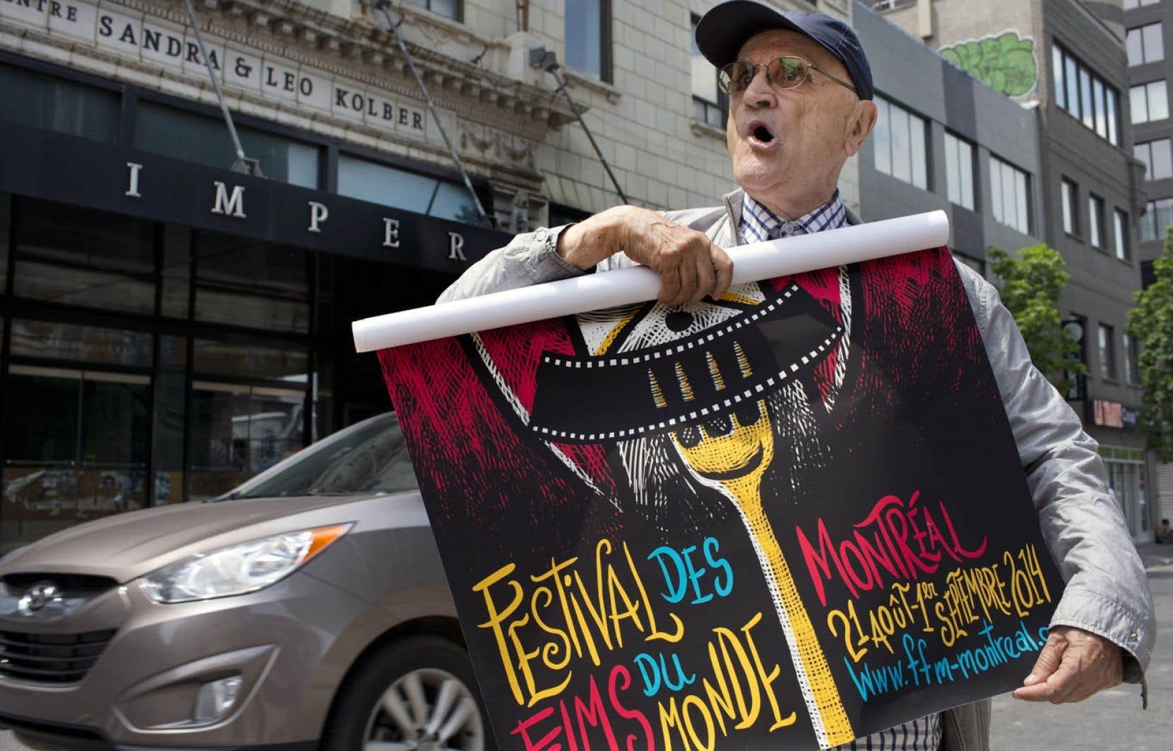 Le président du Festival des films du monde, Serge Losique, photographié devant le cinéma Impérial, mardi, avec l'affiche du 38e festival. Le FFM espère toujours s'entendre avec les bailleurs de fonds pour permettre la tenue du prochain festival, fin août.