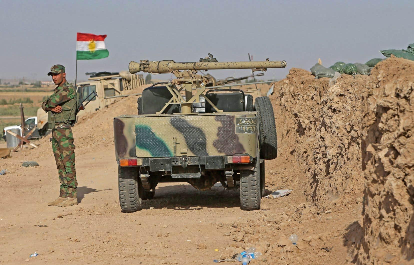 Un combattant kurde surveille des barricades de terre érigées par le gouvernement régional kurde afin de marquer les frontières potentielles d'un futur état indépendant.