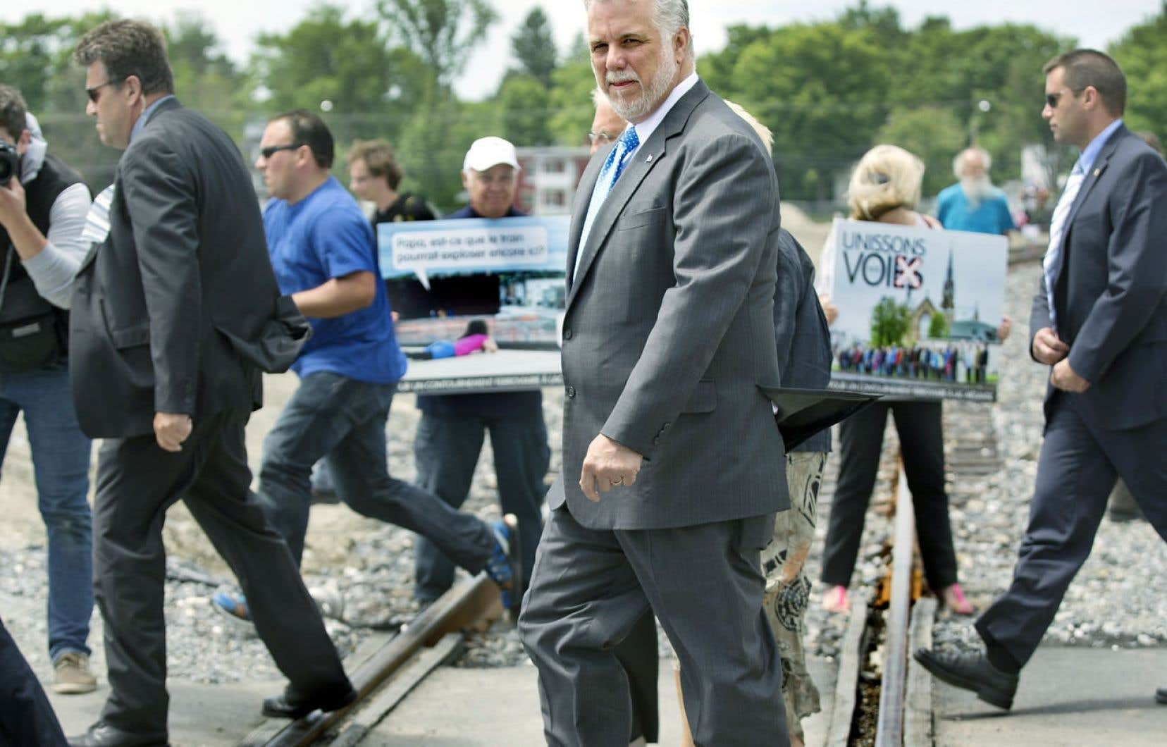 Le premier ministre Philippe Couillard traversant la voie ferrée à Lac-Mégantic, dimanche, devant des manifestants qui ont attiré l'attention des élus sur l'importance d'une voie de contournement pour la municipalité après le déraillement du 6 juillet 2013.