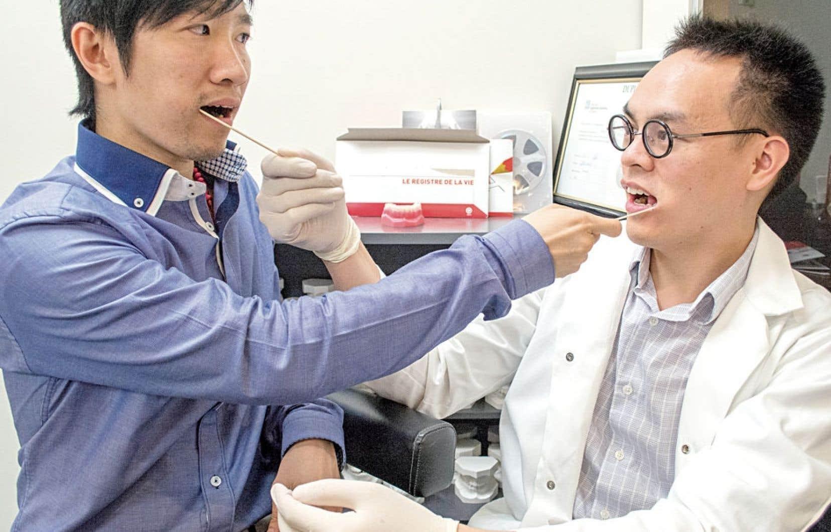 Le dentiste Glenn Hoa (à droite) et Joseph Huynh Ngoc-tri, deux Québécois d'origine vietnamienne, ont volontiers accepté de faire le test de prélèvement de salive pour l'analyse de leur profil génétique. Ce test sera envoyé à ceux qui s'inscriront au registre des donneurs d'Héma-Québec.