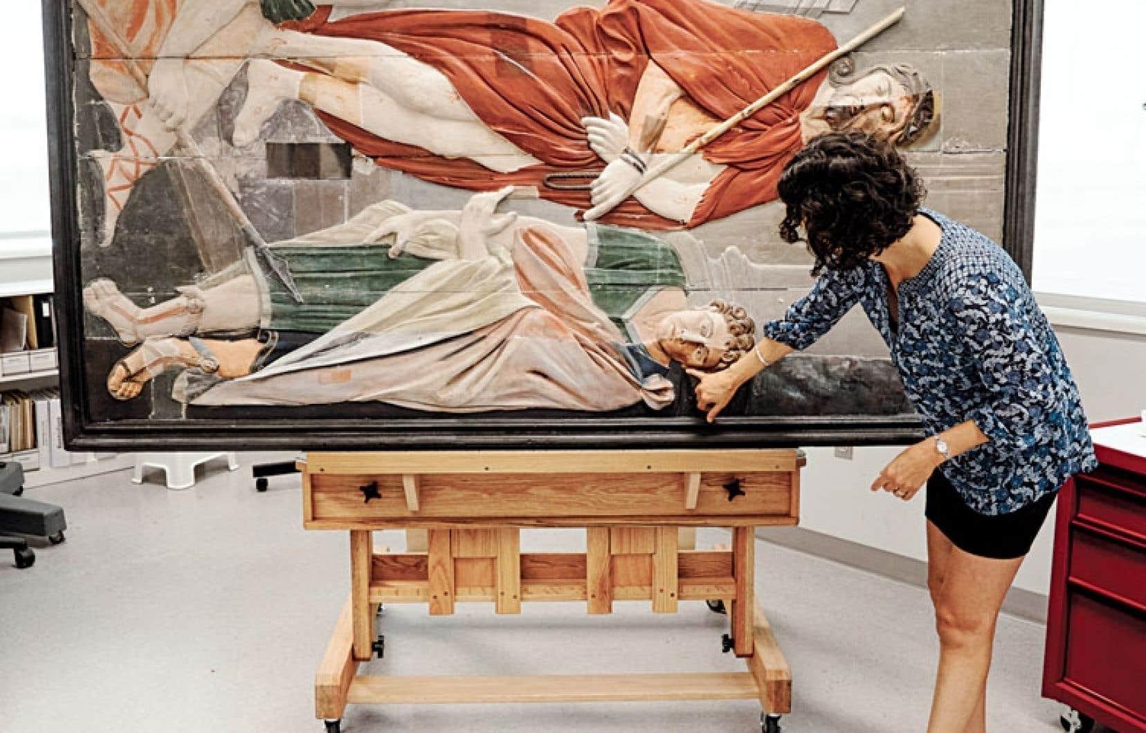 Élisabeth Forest, restauratrice au Centre de conservation du Québec, montrant les premiers résultats des travaux entrepris sur les bas-reliefs du calvaire d'Oka.