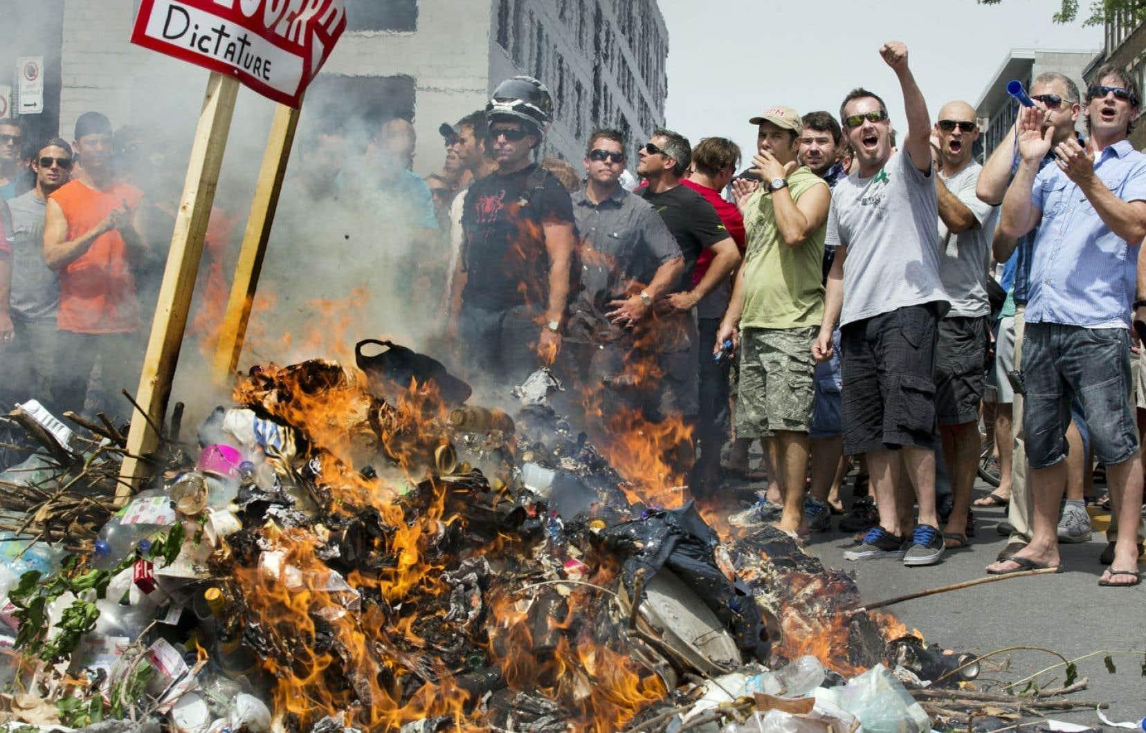 Pompiers, policiers et cols bleus ont créé de toutes pièces un feu de joie en faisant brûler leurs casquettes et des déchets, le 17juin dernier, devant l'hôtel de ville de Montréal.