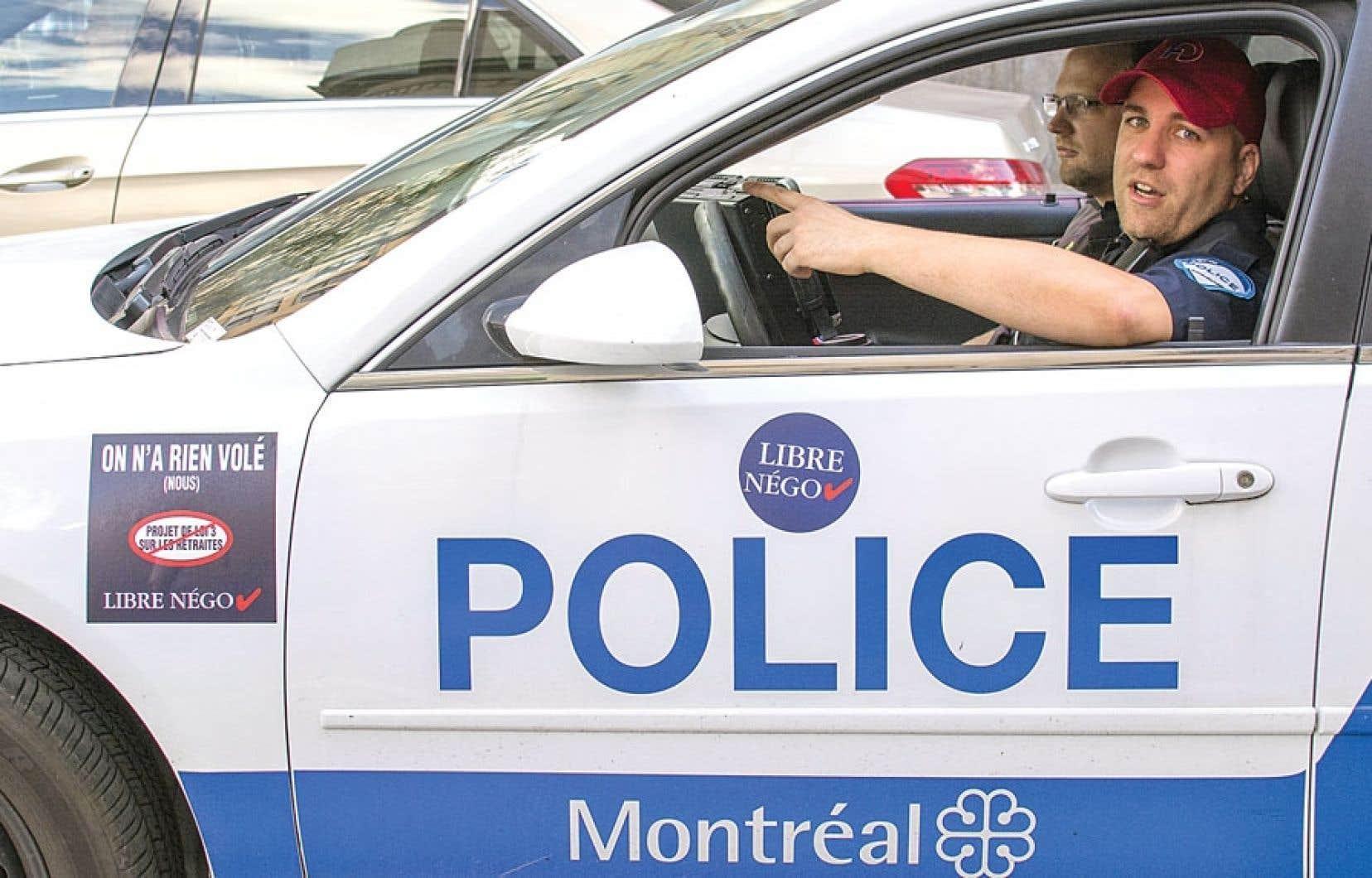 Les policiers de Montréal usent de moyens de pression, comme le port de casquettes rouges et de pantalons de camouflage, pour dénoncer le projet de loi sur les régimes de retraite des employés pour municipaux.