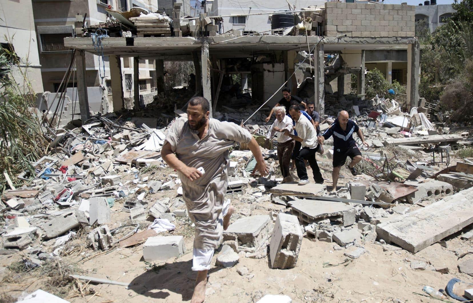 À Gaza, des médecins palestiniens venaient en aide à un survivant, dimanche, après qu'un tir aérien des forces israéliennes eut frappé sa maison.