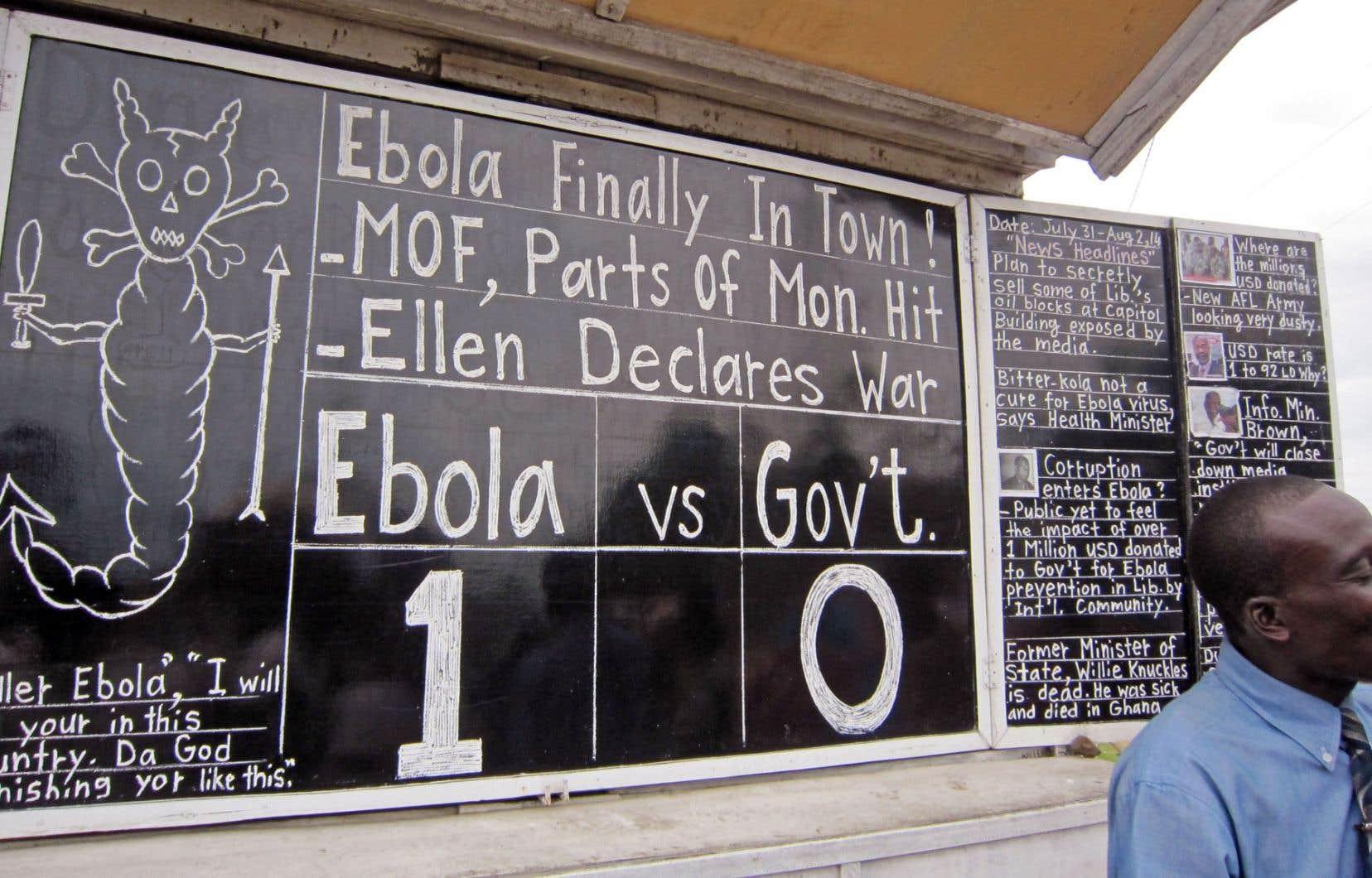 L'orateur public Alfred Sirleaf commente l'actualité, entre autres les ravages du virulent virus Ebola dans quatre pays africains maintenant, en présentant sur son tableau noir les faits saillants à la foule qui se rassemble devant lui sur une place publique de la capitale du Liberia, Monrovia.