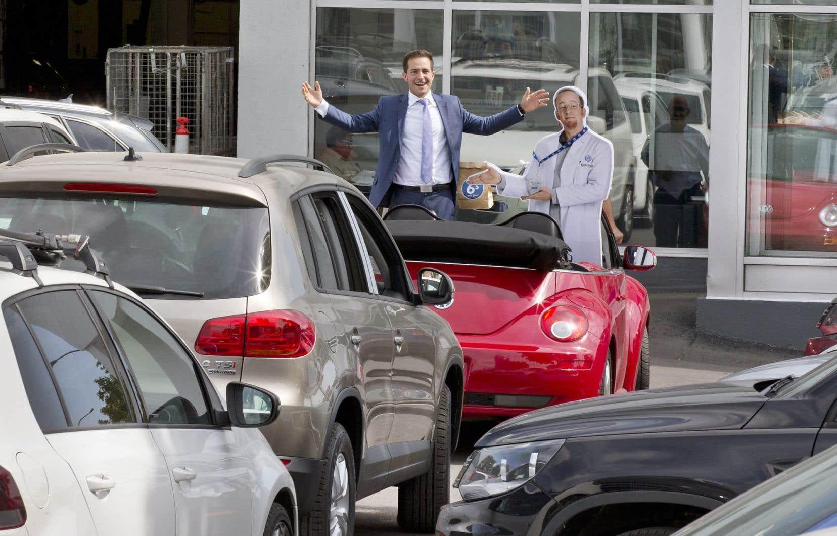 Charles Bassili, le directeur général de Volkswagen Popular, à Montréal, pose à côté d'une pancarte publicitaire qui vante les faibles coûts d'achat d'une voiture. Selon lui, les Québécois adorent les voitures, mais ne veulent pas l'admettre.