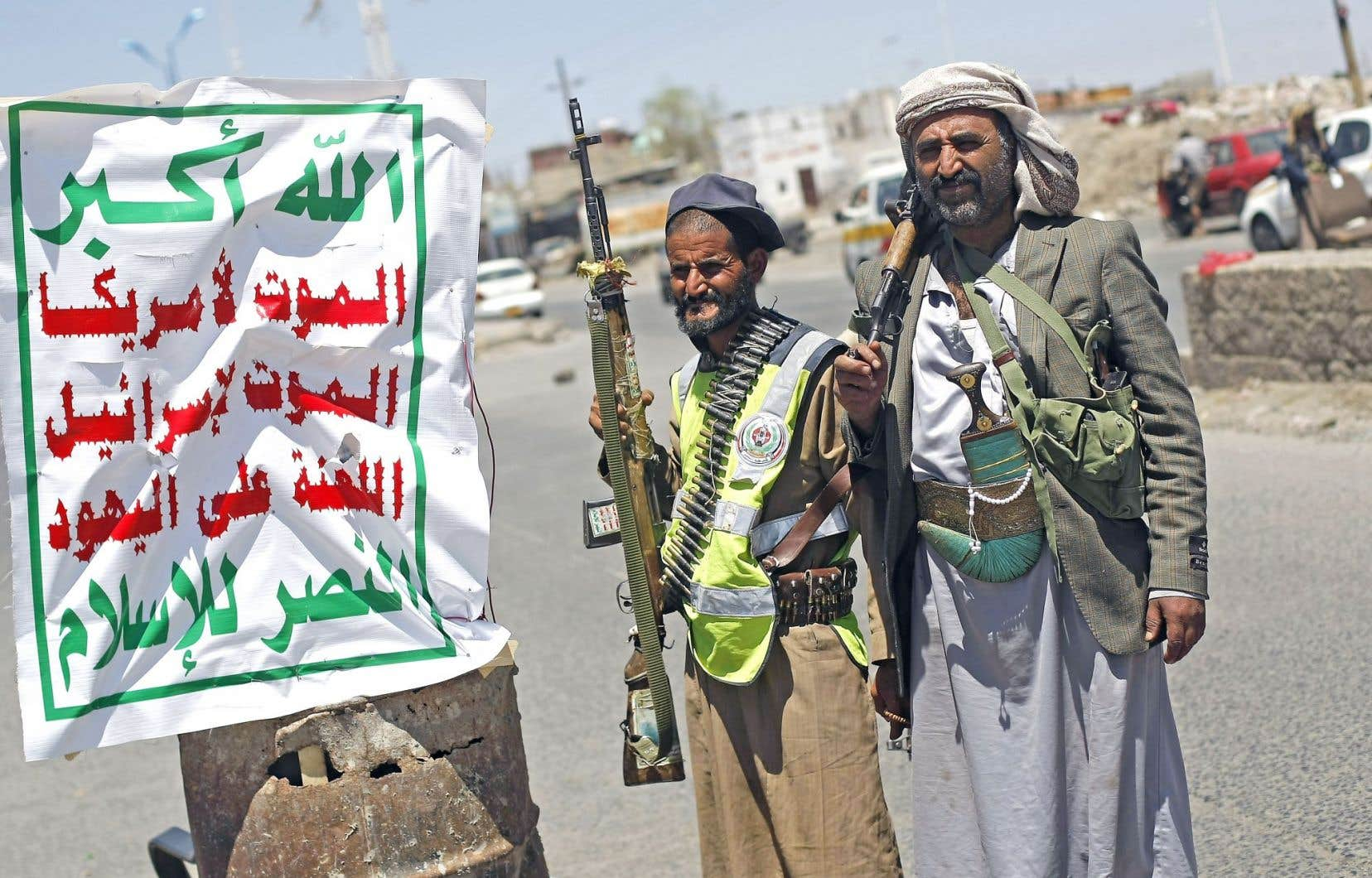 Des rebelles chiites houthis montaient la garde à un point de contrôle près de l'immeuble hébergeant la télévision d'État, dimanche, à Sanaa.