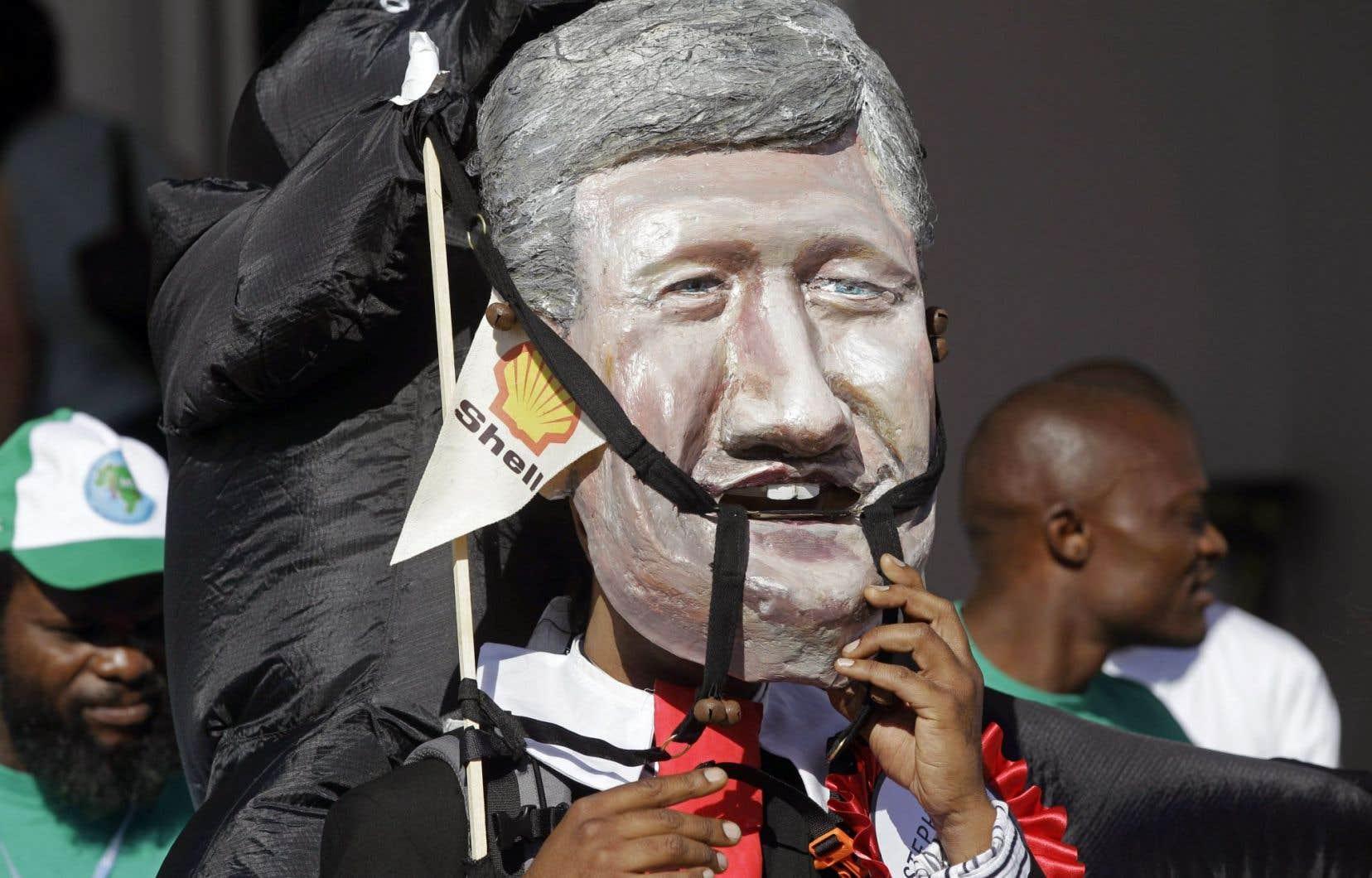 Critiqué de longue date pour ses positions environnementales, Stephen Harper a admis lundi avoir d'autres priorités que de se rendre au Sommet sur le climat. Ci-dessus, un manifestant arborant une tête de Harper en papier mâché au Sommet de Durban, en 2011.