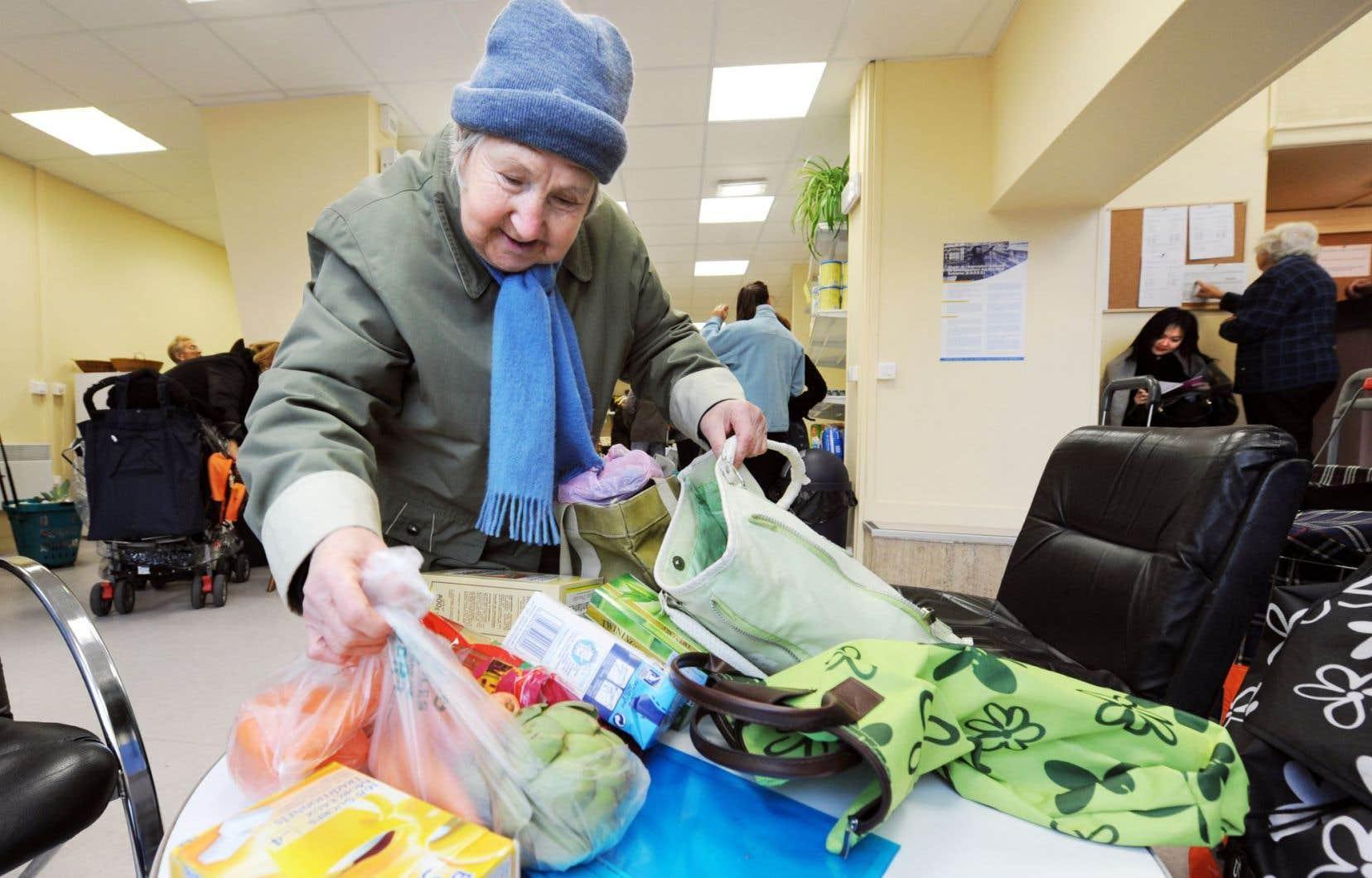 Une femme met dans son sac l'épicerie qu'elle vient de faire dans un centre de dépannage.