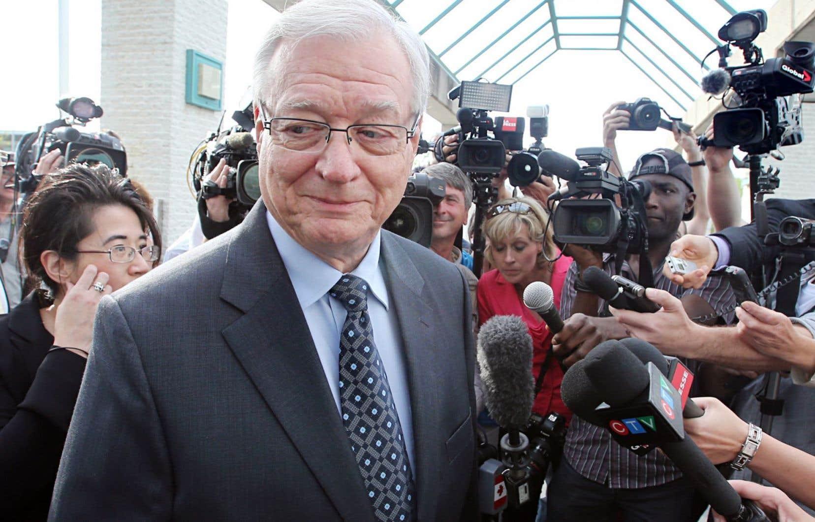 Une mêlée de presse lors de l'arrestation, par l'Unité permanente anticorruption (UPAC), de l'ancien maire de Laval Gilles Vaillancourt, à sa sortie du palais de justice lavallois le 10 mai 2013.