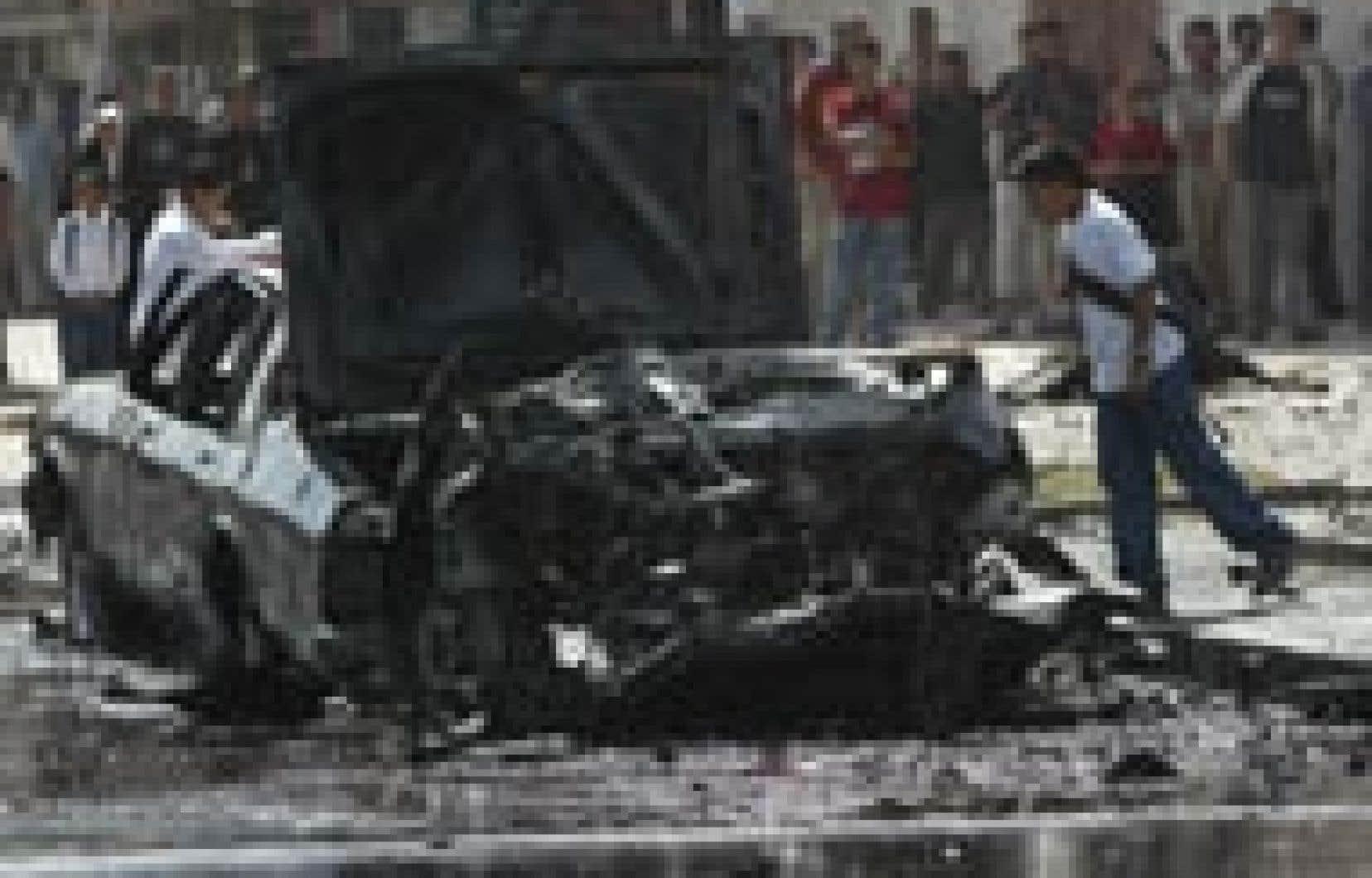 Un écolier irakien regardait un véhicule qui a explosé à Bagdad hier.