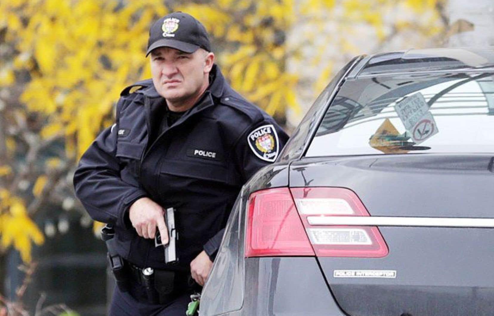 Un policier aux aguets dans le centre-ville d'Ottawa, le 22octobre dernier, à la suite de l'attentat du parlement.
