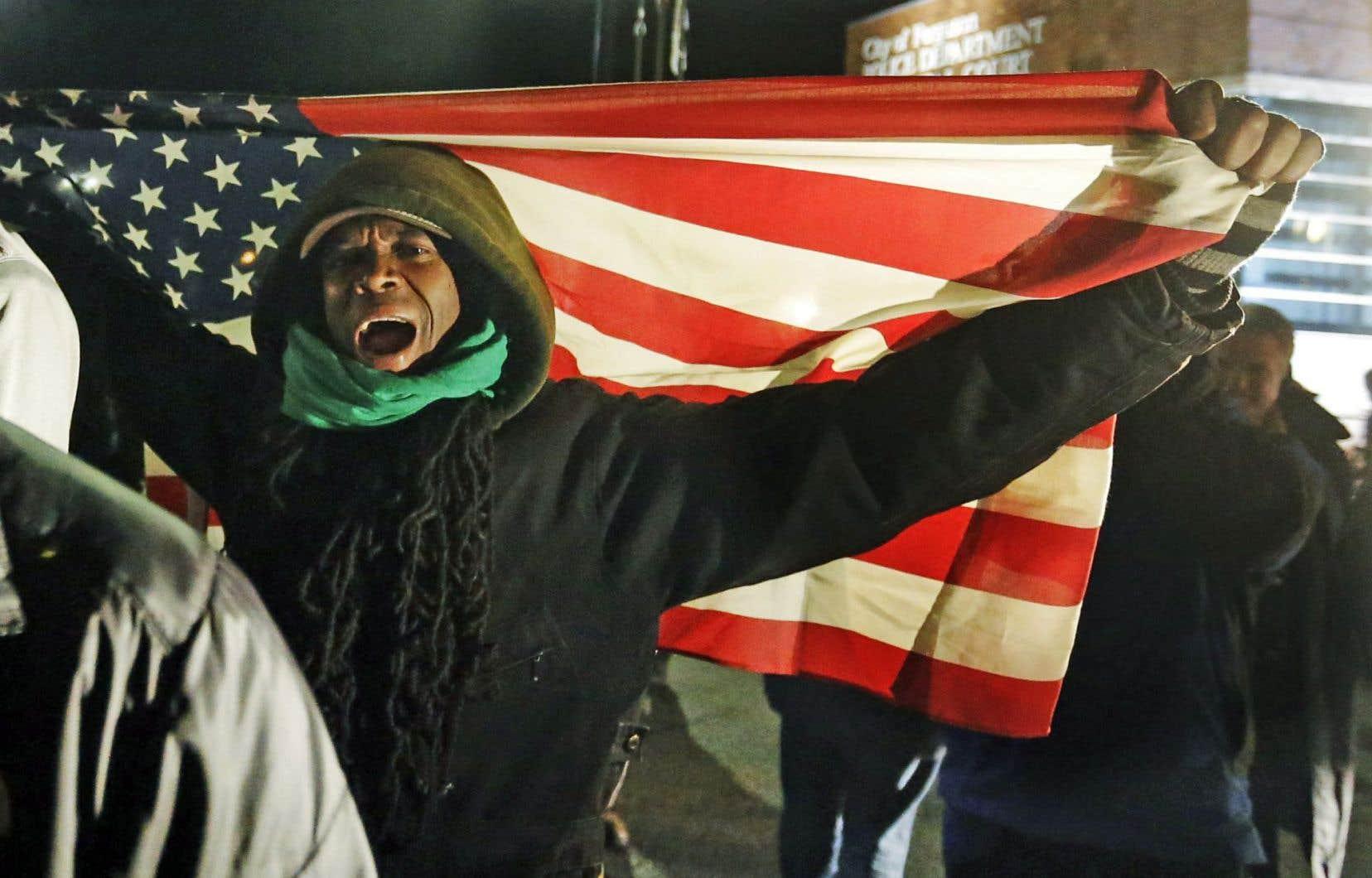 Plus de 2200 militaires de la Garde nationale se sont joints aux policiers pour contrôler la foule des protestataires mardi soir à Ferguson, au Missouri, à la suite d'une nuit d'émeutes. Ci-dessus, des manifestants postés non loin du quartier général de la police.