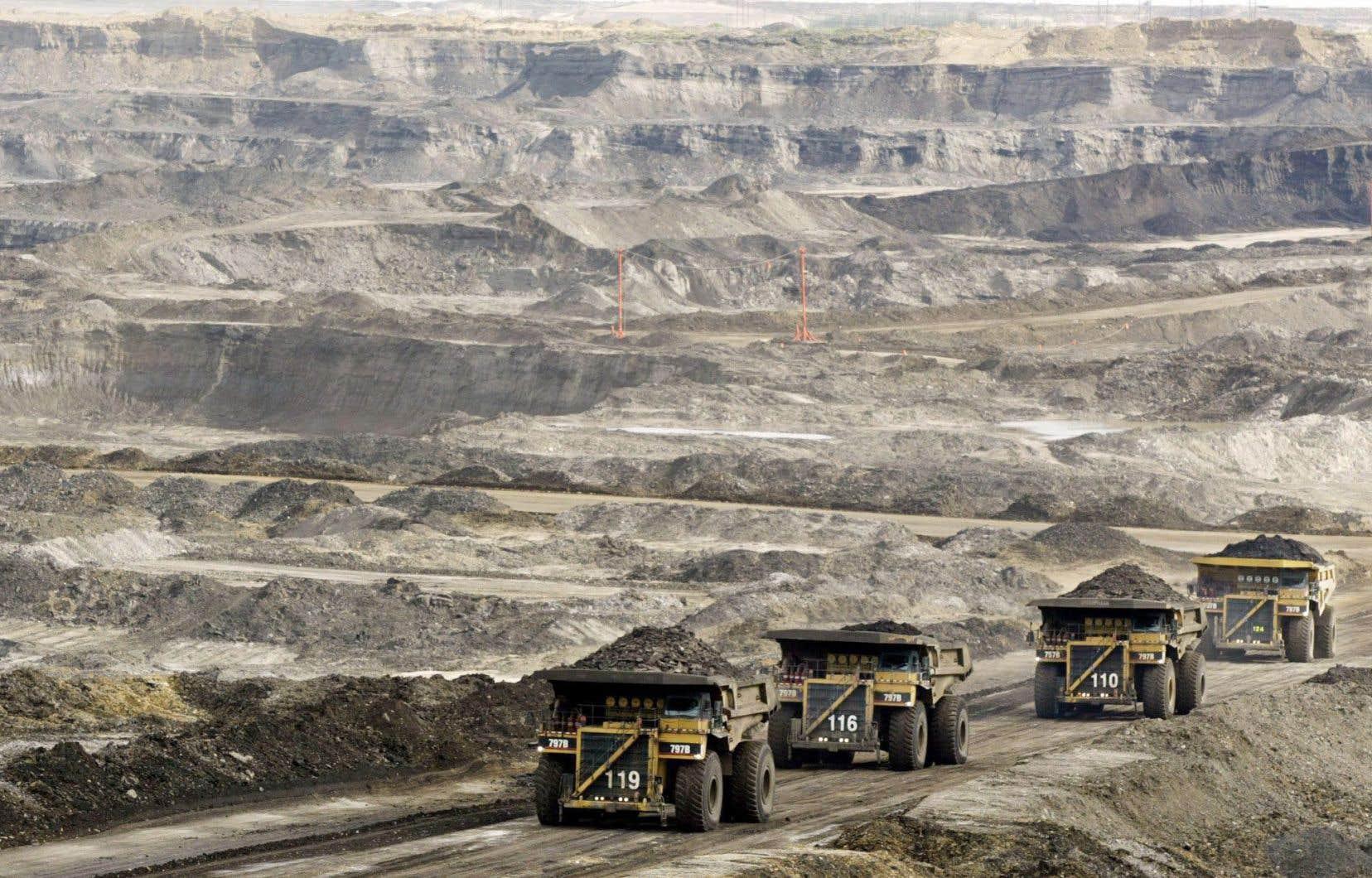 À Fort McMurray, en Alberta, des mastodontes chargés de sables bitumineux se dirigent vers l'usine de transformation.