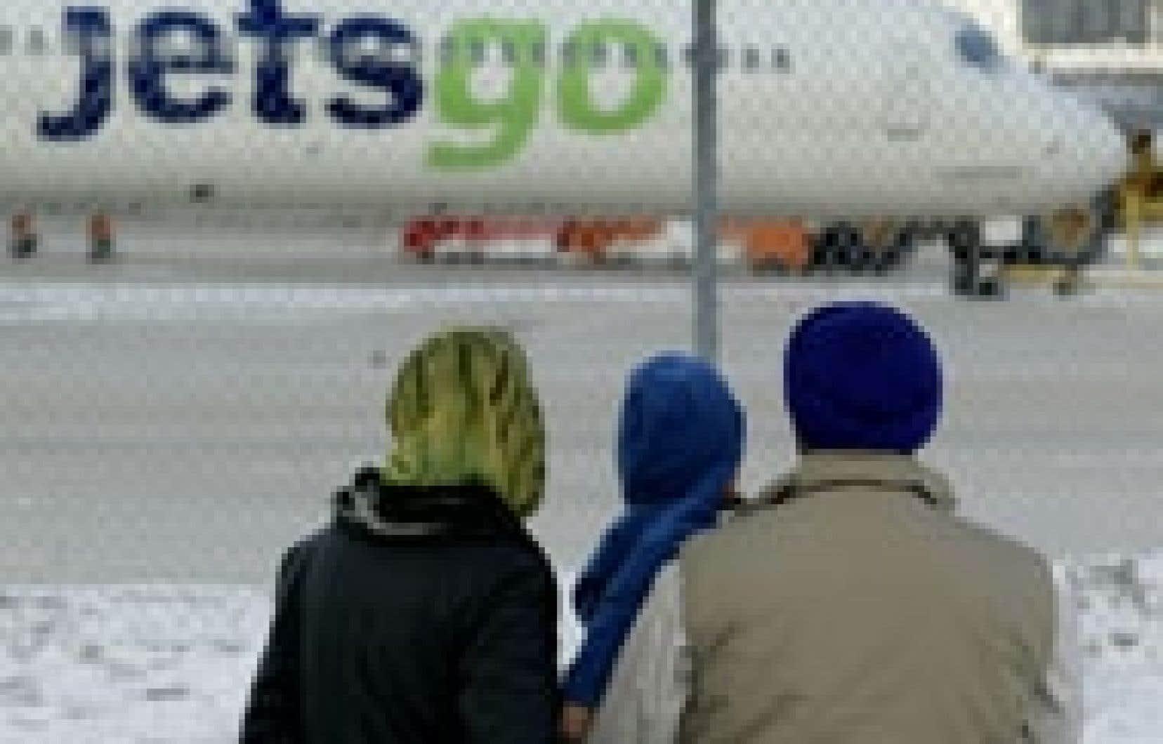 Une famille observe un avion de Jetsgo immobilisé à l'aéroport Pearson après l'annonce de l'arrêt des vols de l'entreprise, le 11 mars dernier. À ce moment, le transporteur devait 108 millions à ses fournisseurs, à ses clients, à ses pil