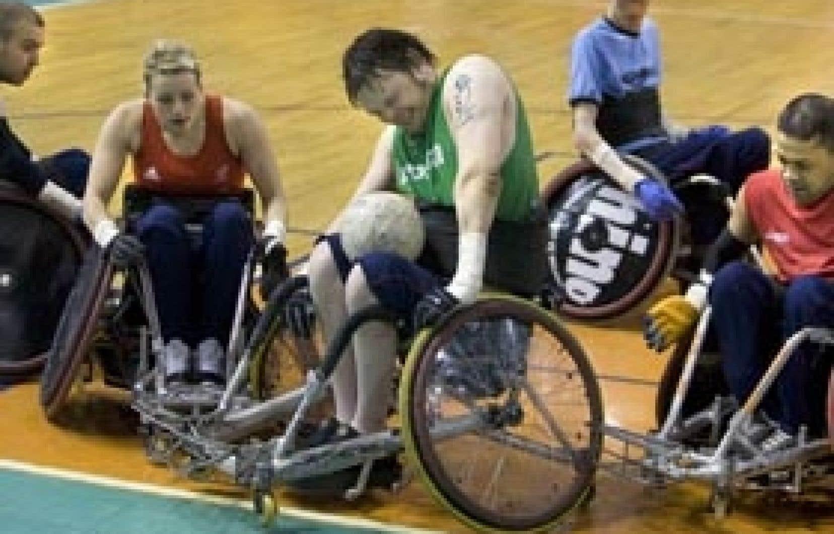 En possession du ballon et sous le regard de ses coéquipiers Jonathan Coogan et Josie Pearson, Jason Roberts tente de s'extirper d'une mêlée lors d'une séance d'entraînement de l'équipe britannique de rugby en fauteuil roulant GB All-Star