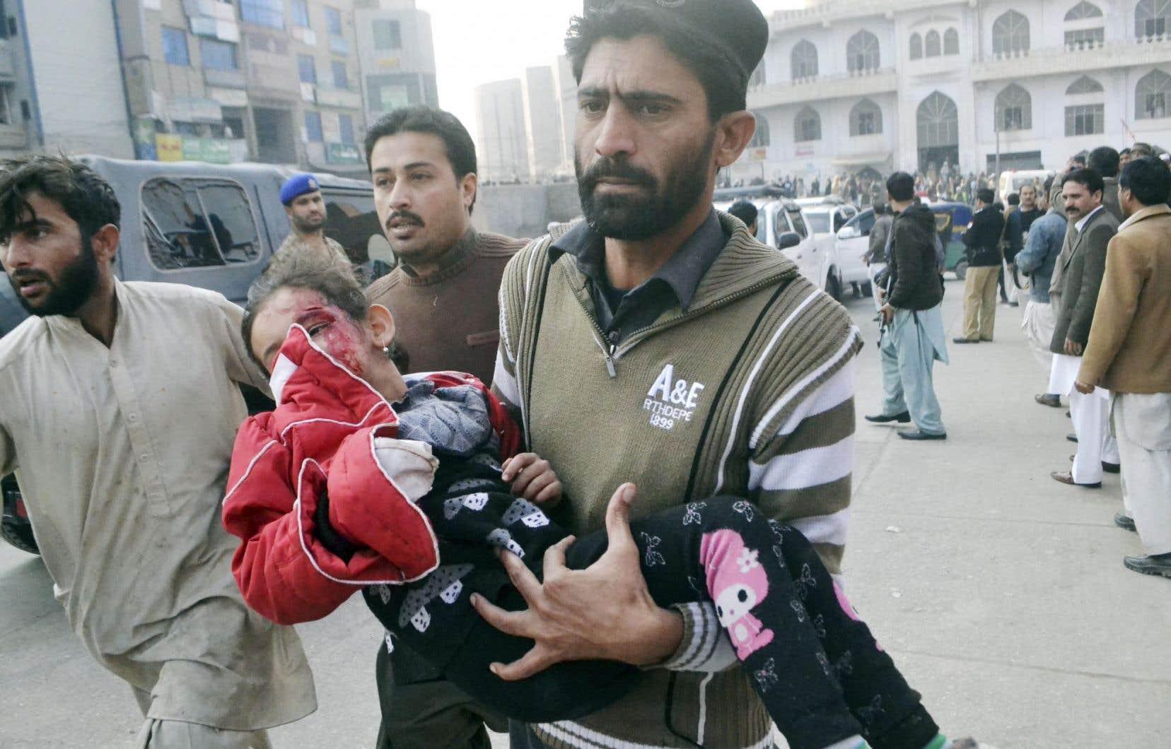 Une fillette blessée est transportée vers un hôpital de Peshawar, au Pakistan, après le massacre perpétré mardi par des talibans dans une école.