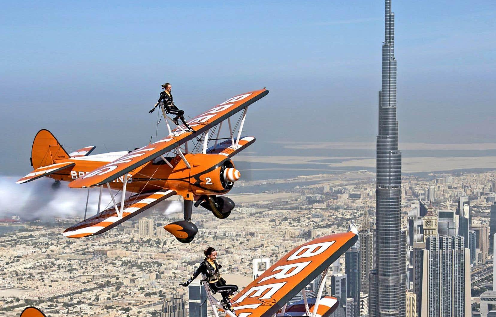 Des acrobates participent à un spectacle aérien au-dessus de l'émirat. En arrière-plan, le plus haut gratte-ciel du monde.
