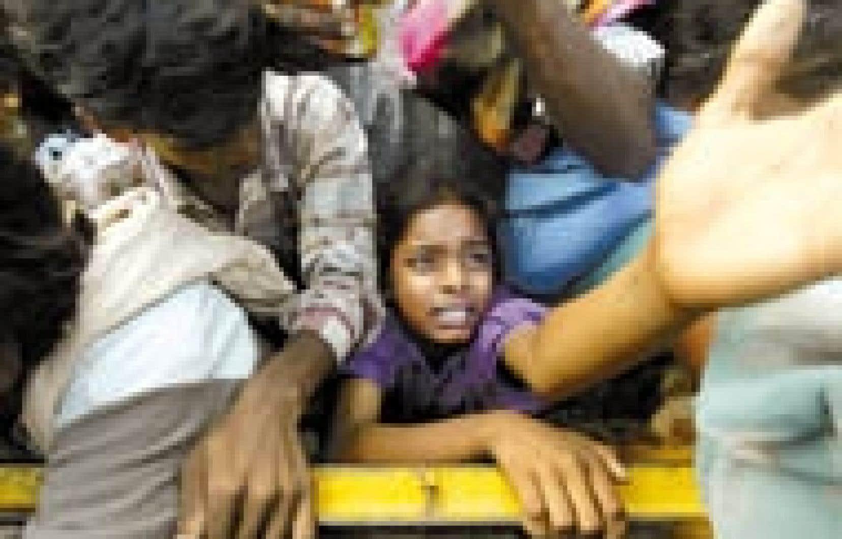 Un enfant tend la main parmi la foule des sinistrés pour recevoir de la nourriture et des vêtements, à Cuddalore, au sud de Madras, en Inde.