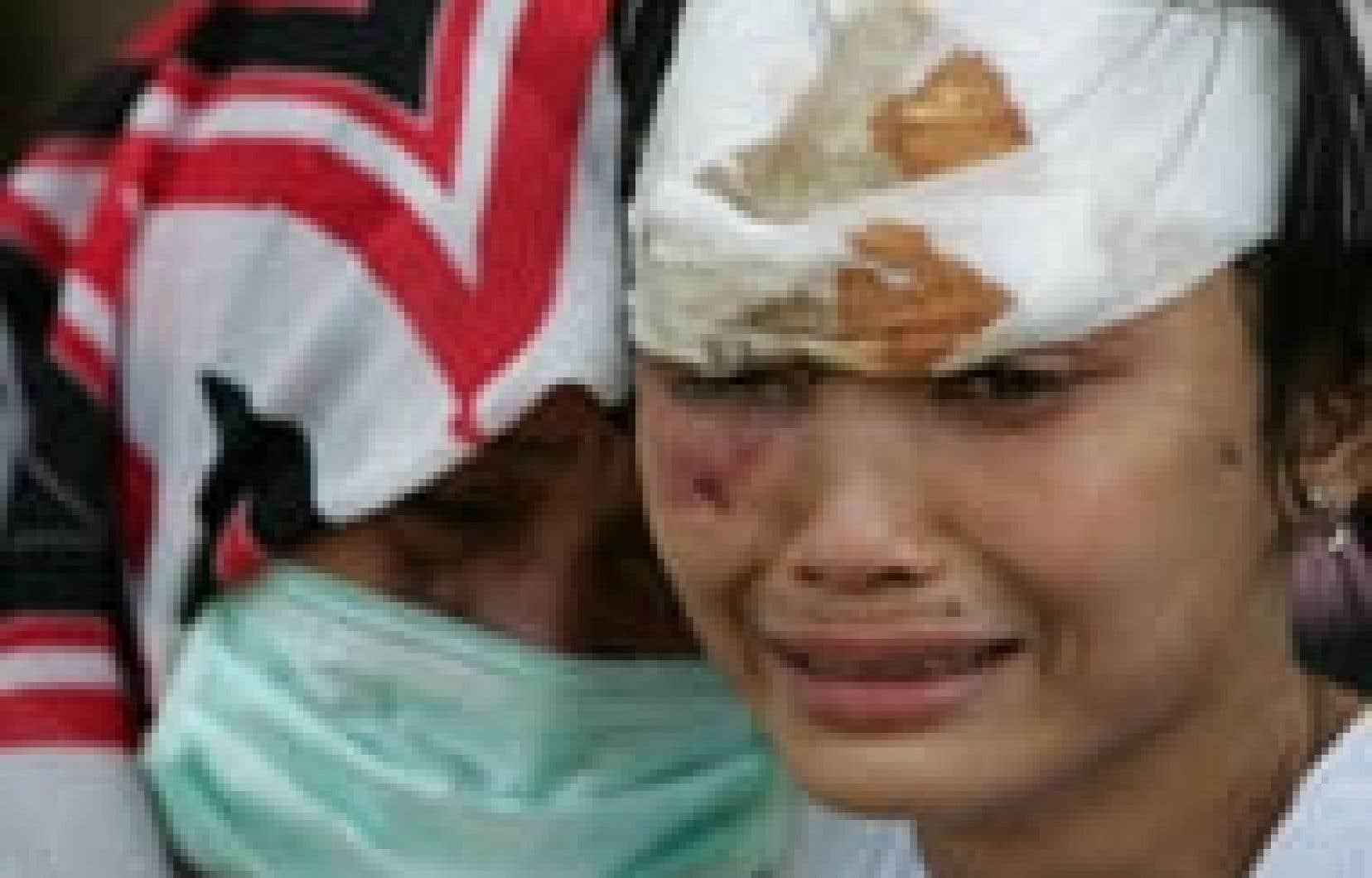 Deux femmes en pleurs attendent pour recevoir des soins dans un hôpital militaire à Banda Aceh, en Indonésie. Le vice-président du pays a annoncé hier que le total des victimes en Indonésie dépassait les 40 000 personnes.
