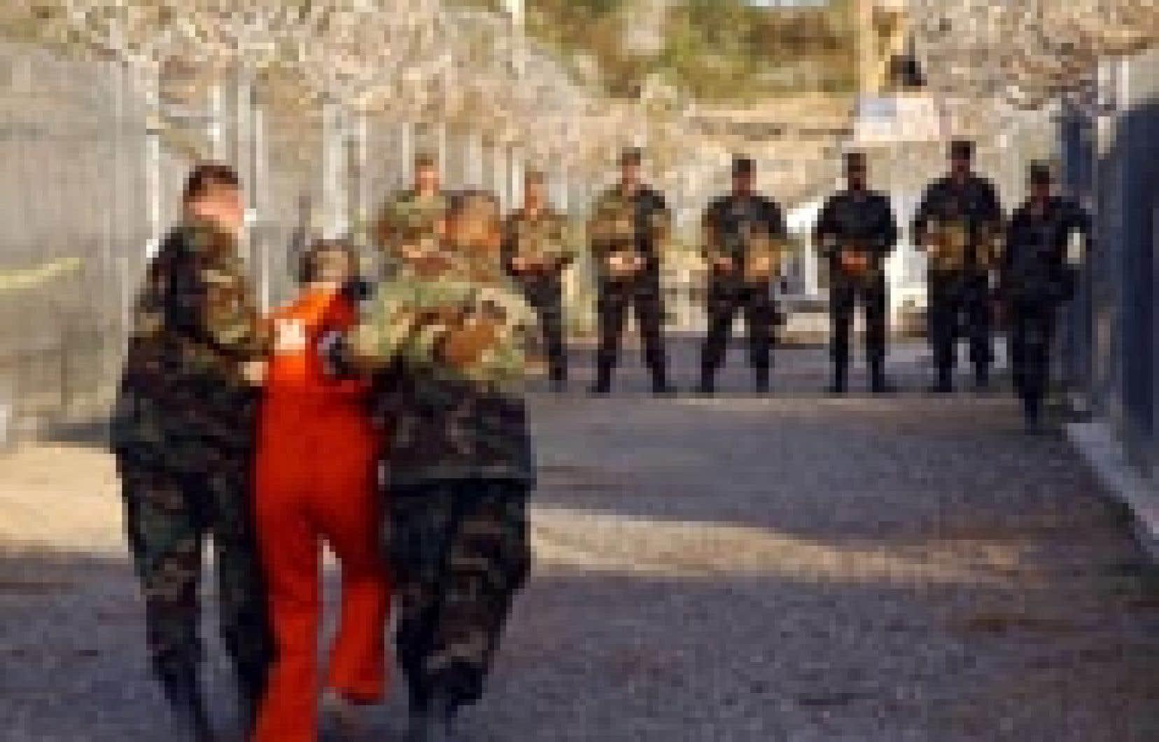 Un policier militaire escortait un prisonnier, en janvier 2002, jusqu'à sa cellule au camp X-Ray sur la base navale de Guantanamo.