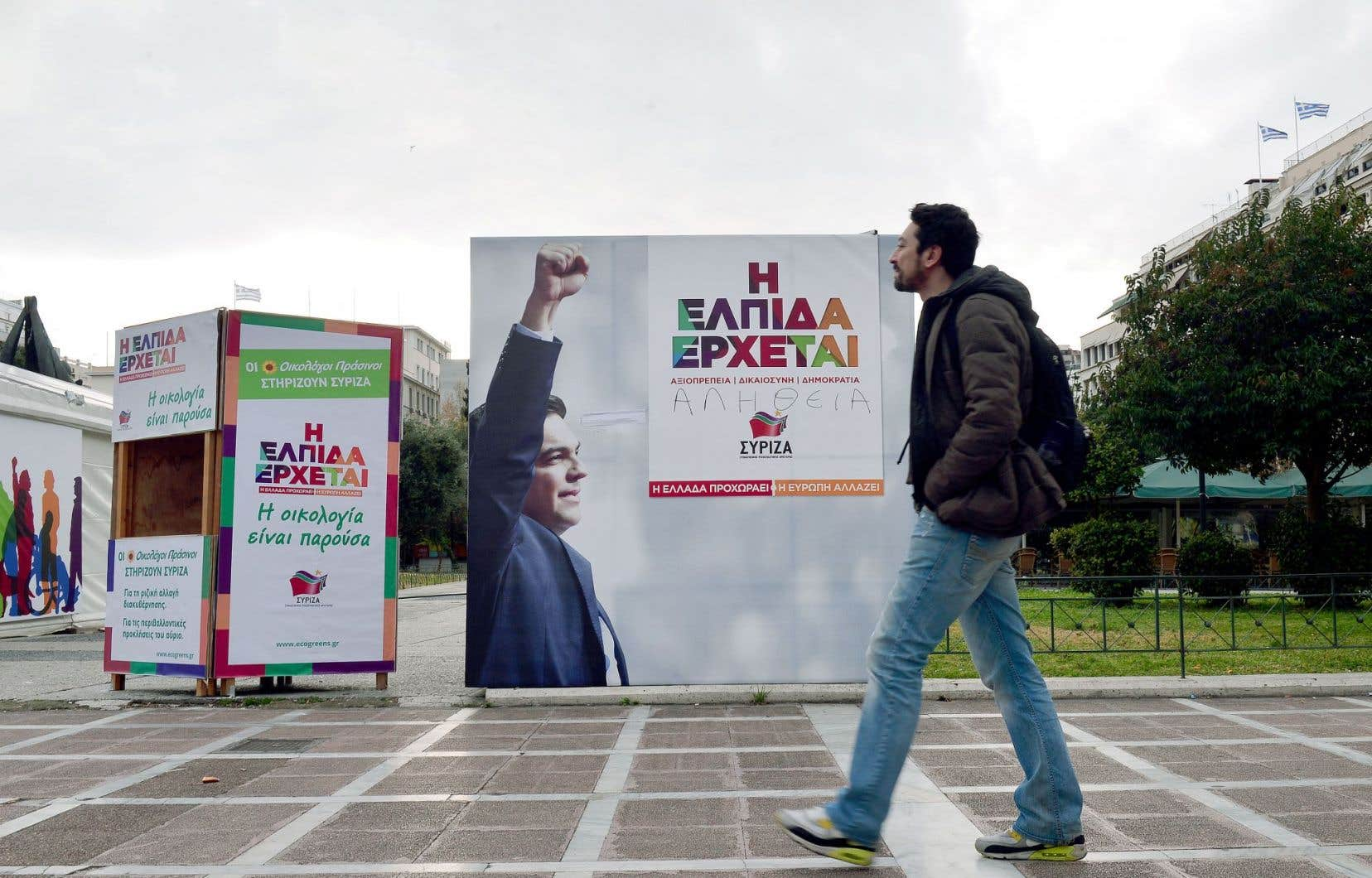 À Athènes, un homme passe devant une affiche appelant à voter pour le parti Syriza d'Alexis Tsipras, une formation anti-austérité en avance dans les sondages.