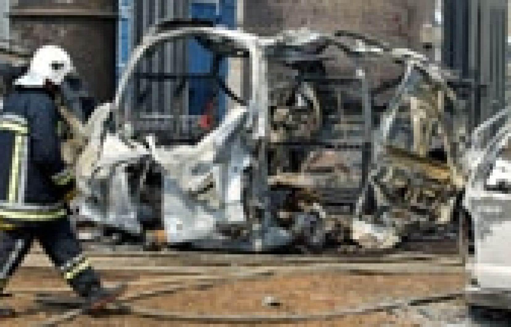 Un pompier belge passe devant des carcasses de véhicules laissées par l'explosion.