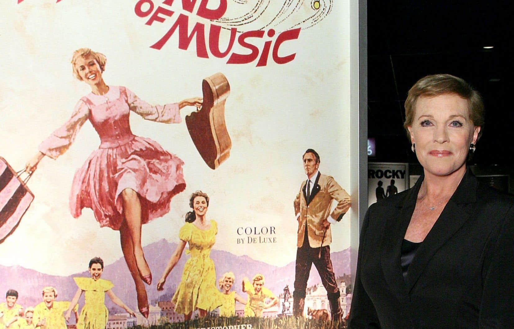 Julie Andrews, qui a bien profité de son triomphe, pose fièrement devant l'affiche du film.