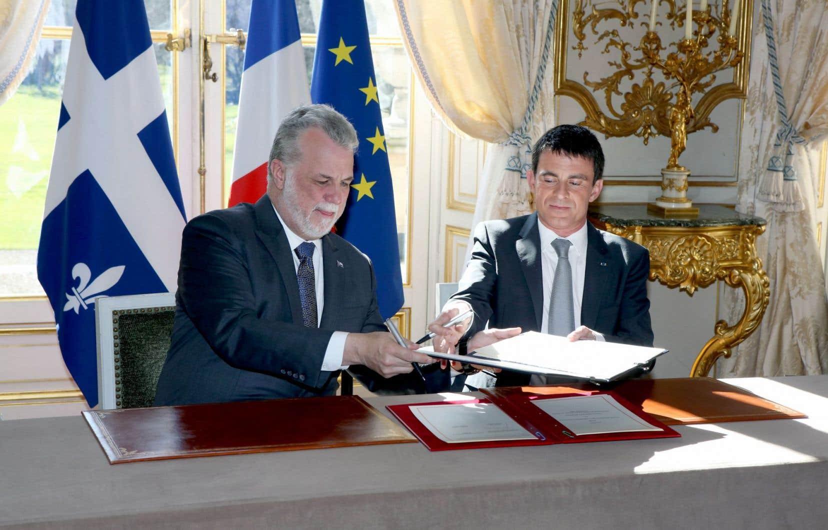 Les premiers ministres québécois, Philippe Couillard, et français, Manuel Valls, signent le «relevé de décisions» publié à l'issue de la 18e «rencontre alternée», qui s'est tenue vendredi à Matignon.