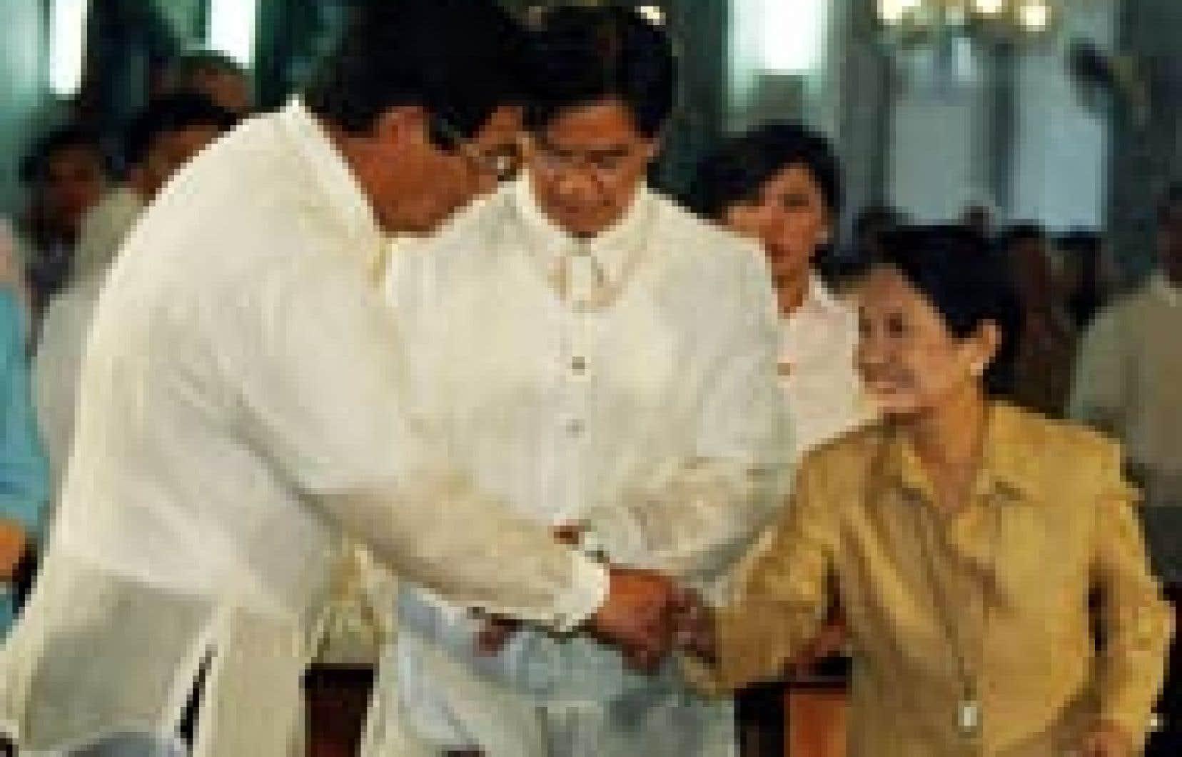 La présidente sortante, Gloria Macapagal Arroyo, serre la main de son principal adversaire à la présidentielle d'aujourd'hui, l'acteur Fernando Poe Jr., au cours d'un service religieux célébré hier à Manille.
