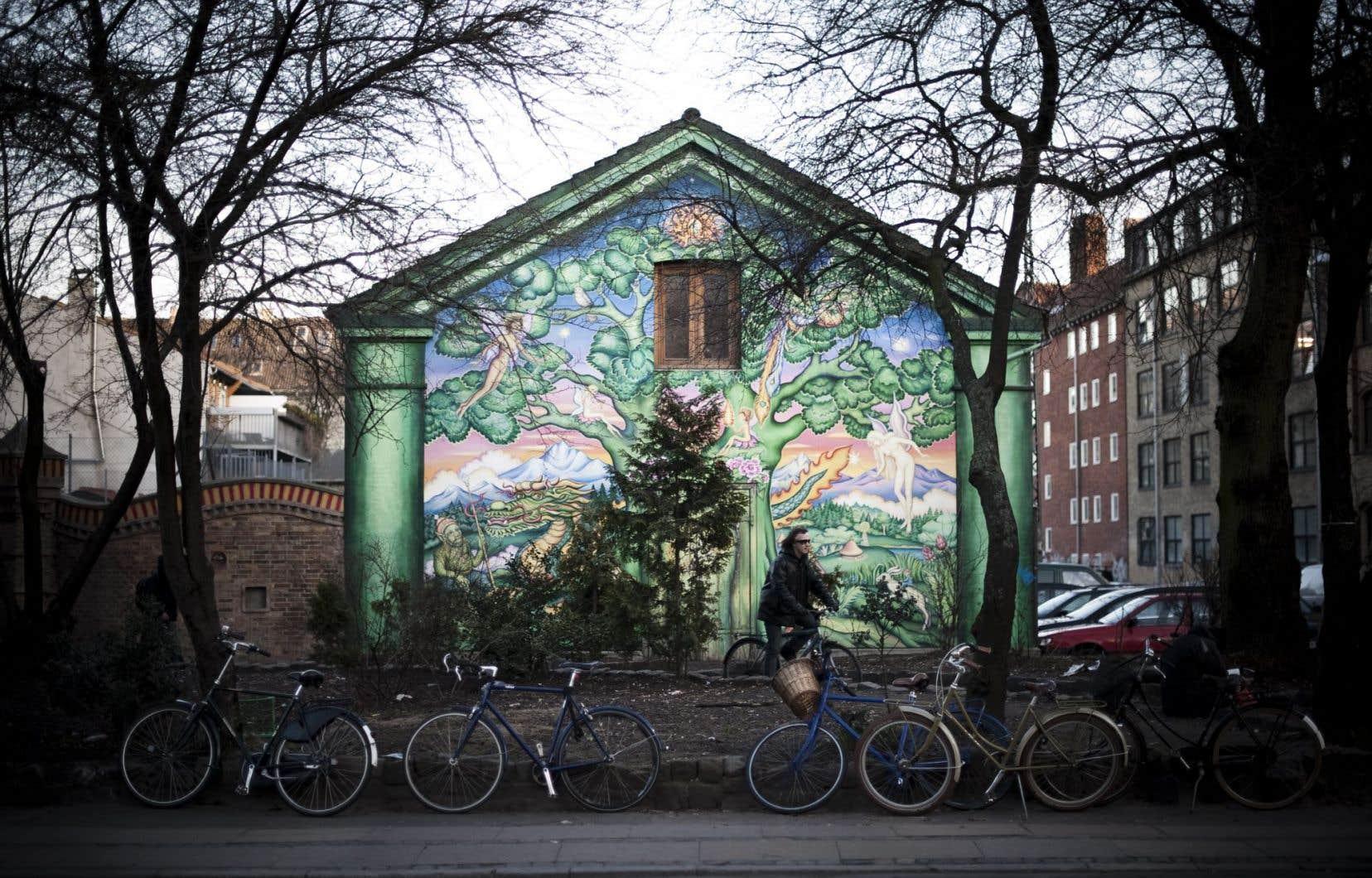 Un homme passe à vélo devant l'une des maisons peintes de Christiania, où vivent en commune libre des centaines de résidants depuis 1971.