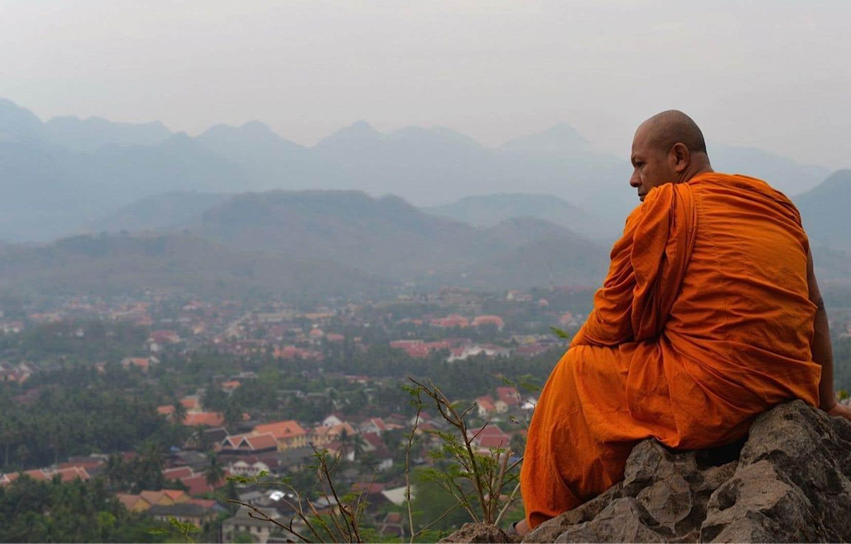Moine jetant un coup d'oeil sur la ville de Luang Prabang, au Laos.<br />