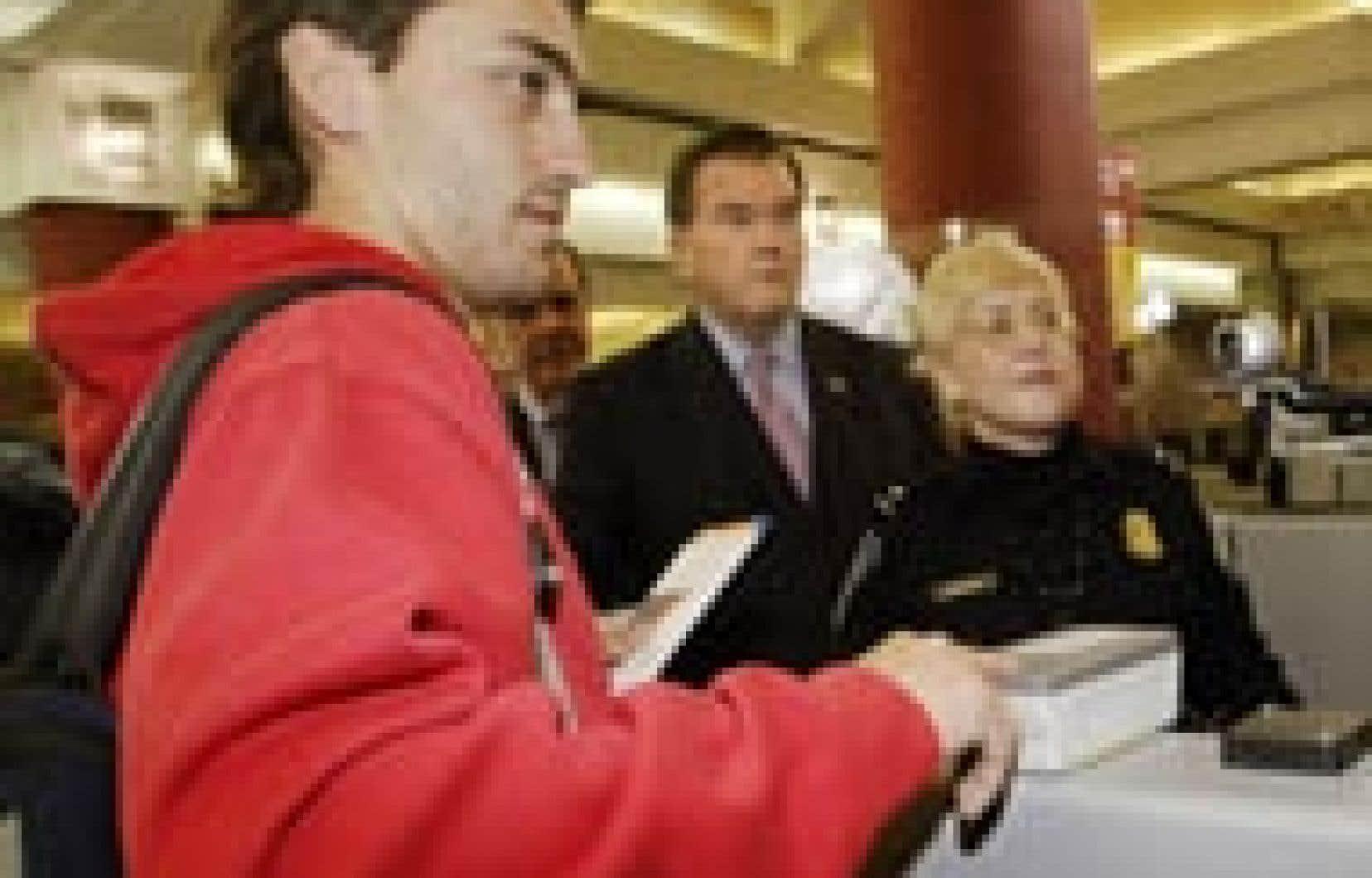 Un voyageur fait prélever ses empreintes sous l'oeil de Tom Ridge (au centre).