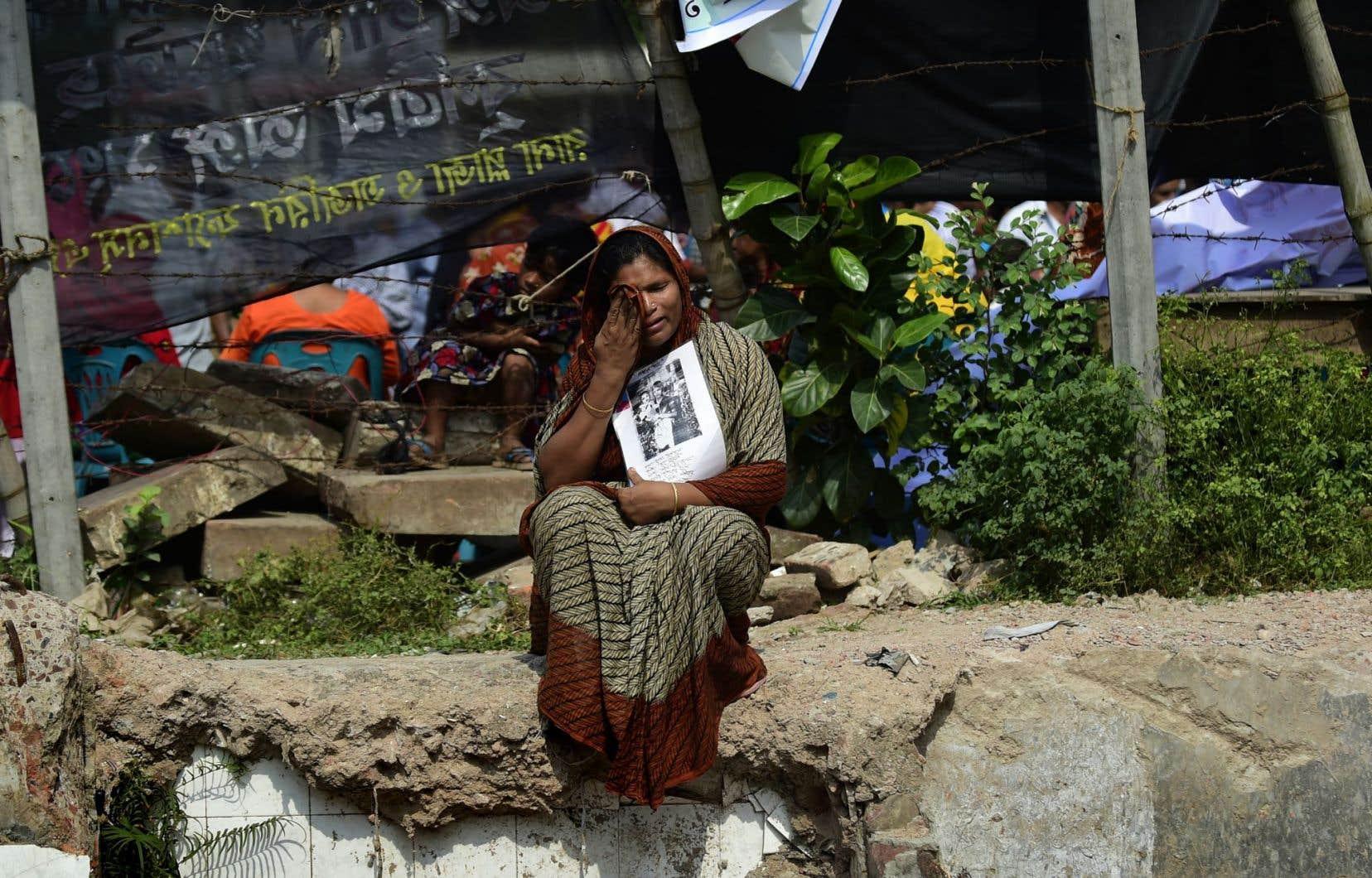 Assise sur les lieux où se trouvait le Rana Plaza, une femme pleure la perte d'un parent dans l'effondrement de l'usine, qui a fait plus de 1100 morts.