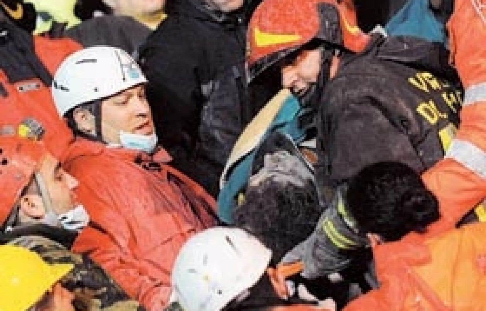 Des secouristes dégagent un blessé des décombres à L'Aquila, ville historique située à l'épicentre du séisme qui a frappé le centre de l'Italie hier.