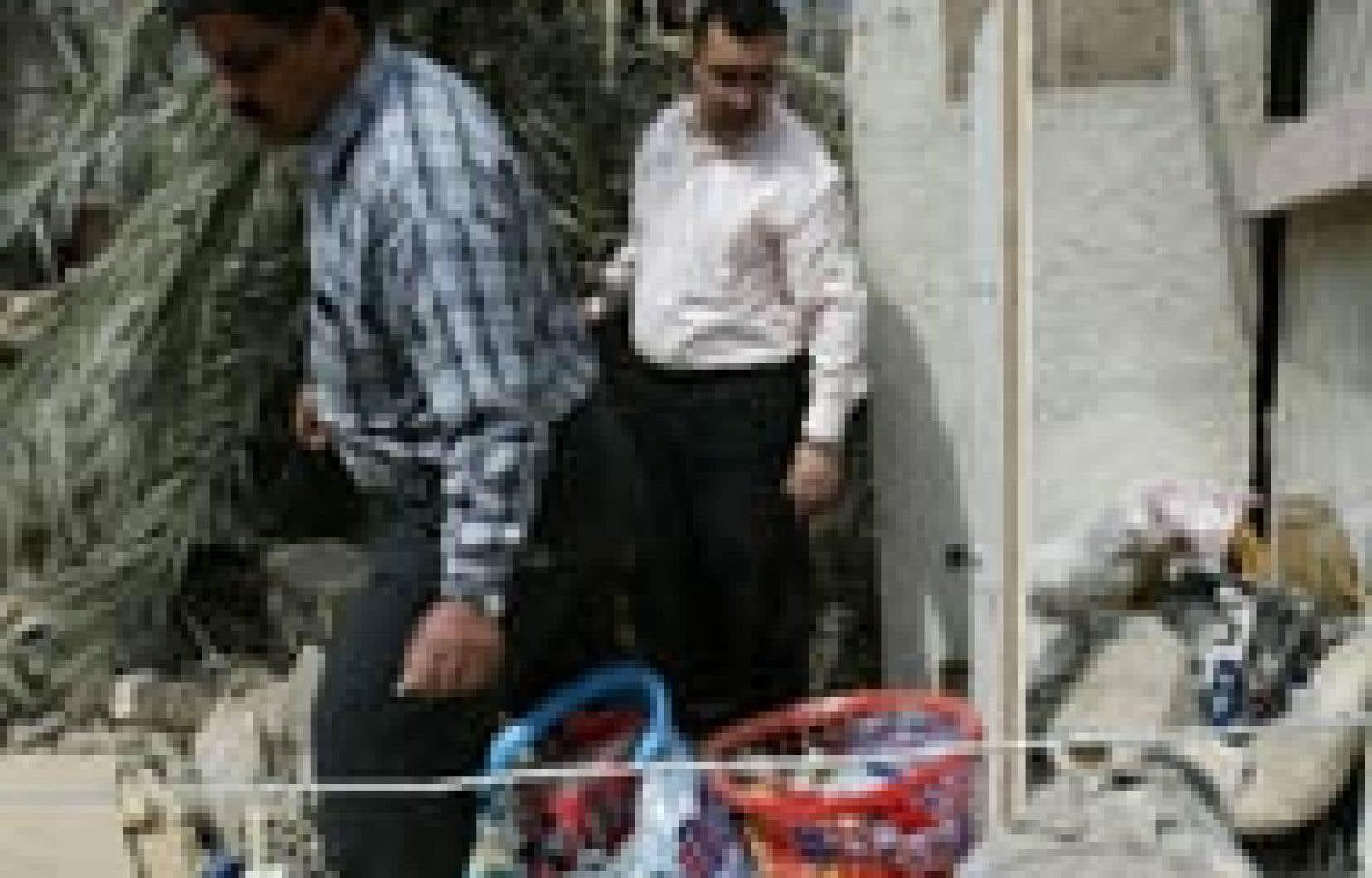 Des Bagdadiens fouillent les décombres de leur maison détruite par un missile américain.
