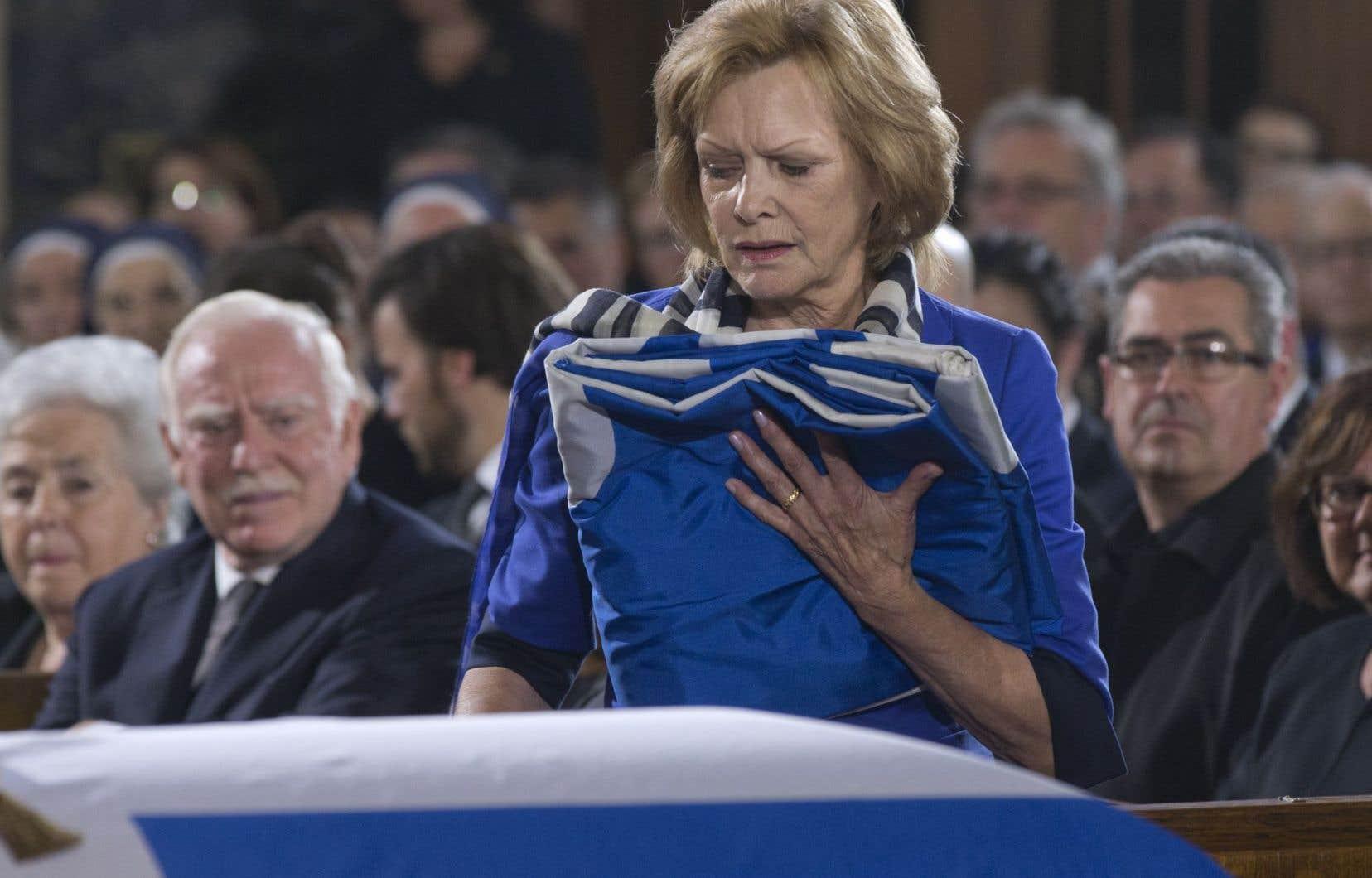 Lisette Lapointe s'est fait remettre un drapeau du Québec à la fin de la cérémonie. À gauche, Robert Parizeau, le frère du défunt.
