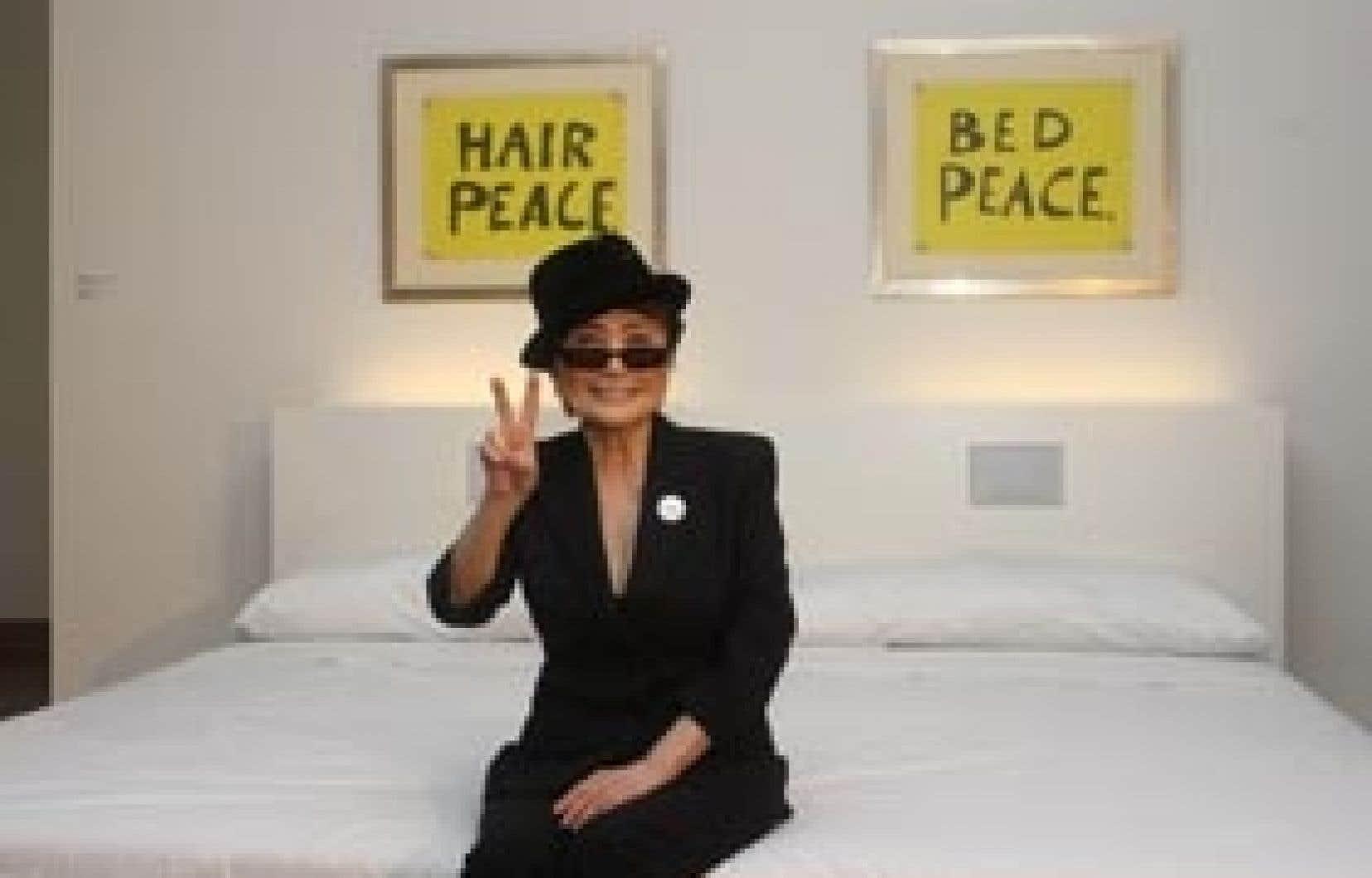 Yoko Ono assise sur le grand lit blanc de l'exposition du Musée des beaux-arts, comme en 1969.