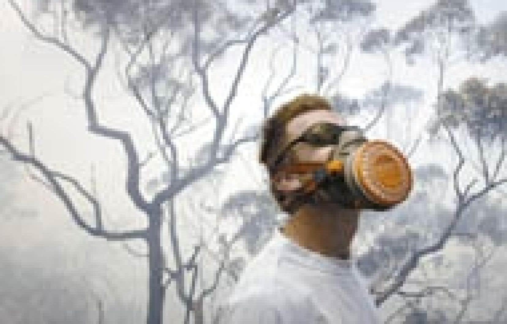 Muni d'un masque à gaz, ce résidant de la banlieue nord de Sydney, en Australie, jette un regard en direction d'un hélicoptère qui participe aux vastes opérations de lutte contre les incendies près de son domicile.
